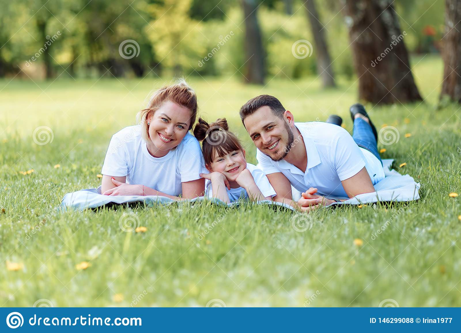 Happiness and harmony in family life. Happy family concept. Young mother and father with their daughter in the park