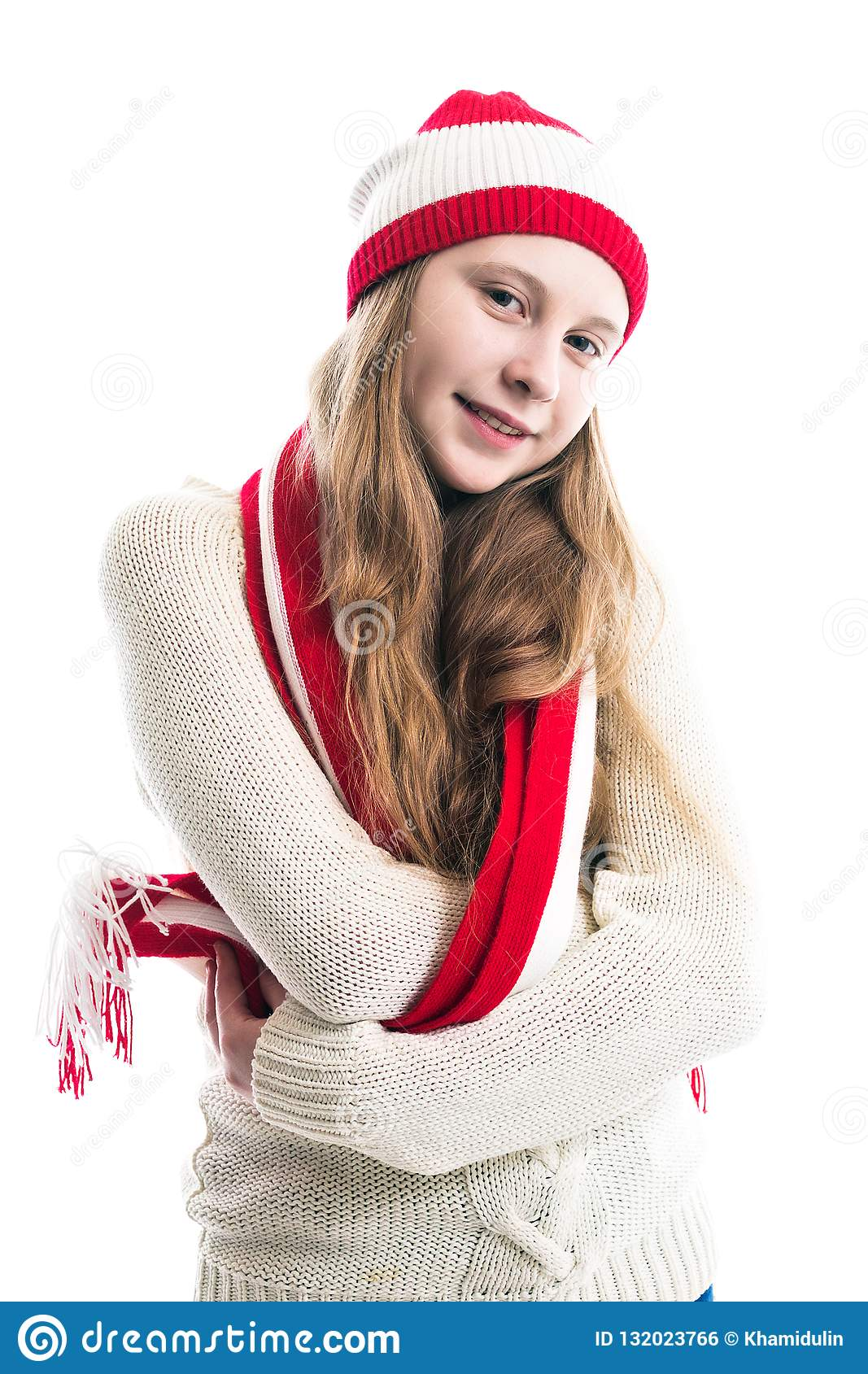 Happiness winter holidays christmas. Teenager concept - smiling young woman in red hat, scarf and over white background.