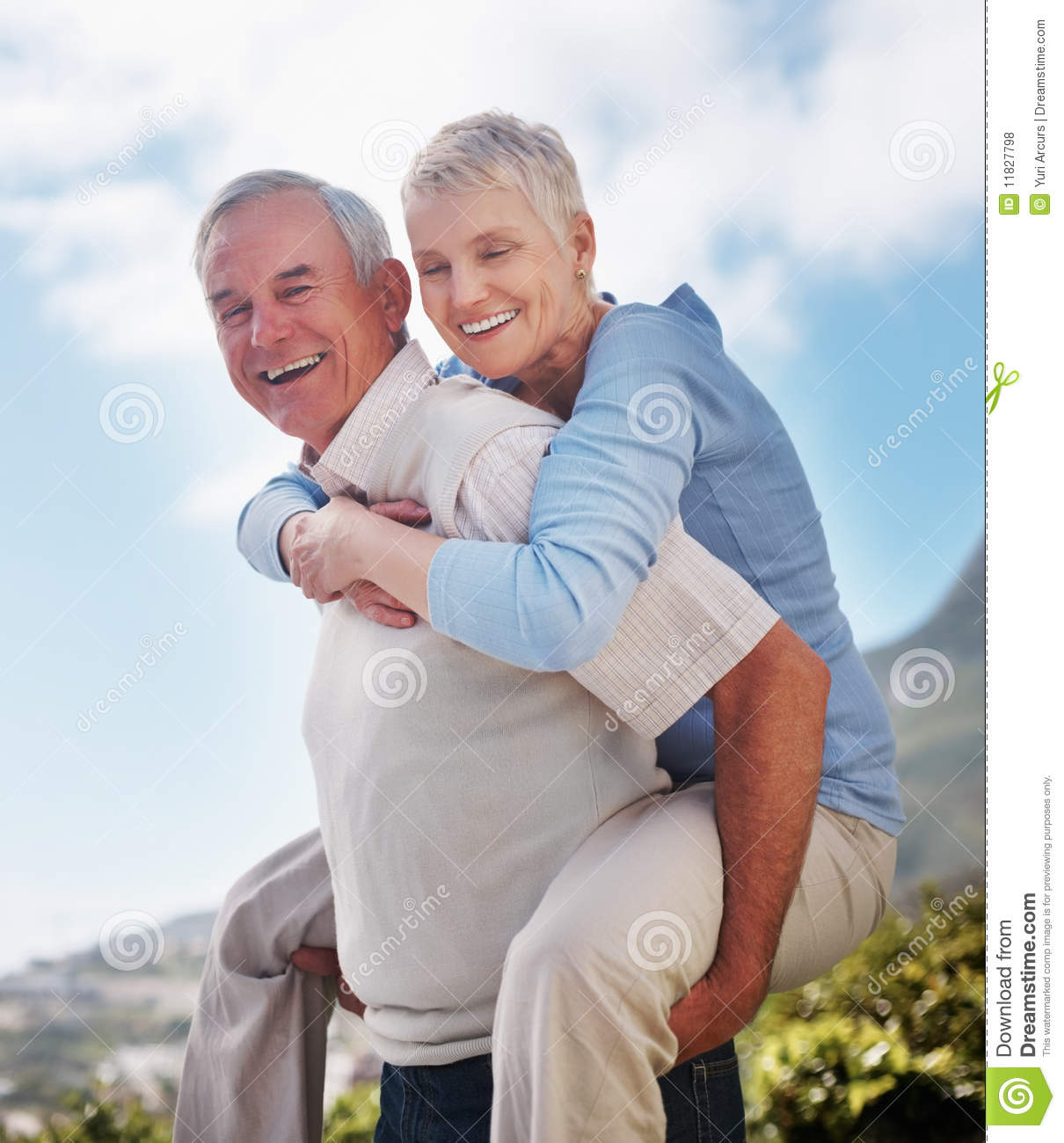Happy Active Older Man Giving Woman Piggyback Ride Stock