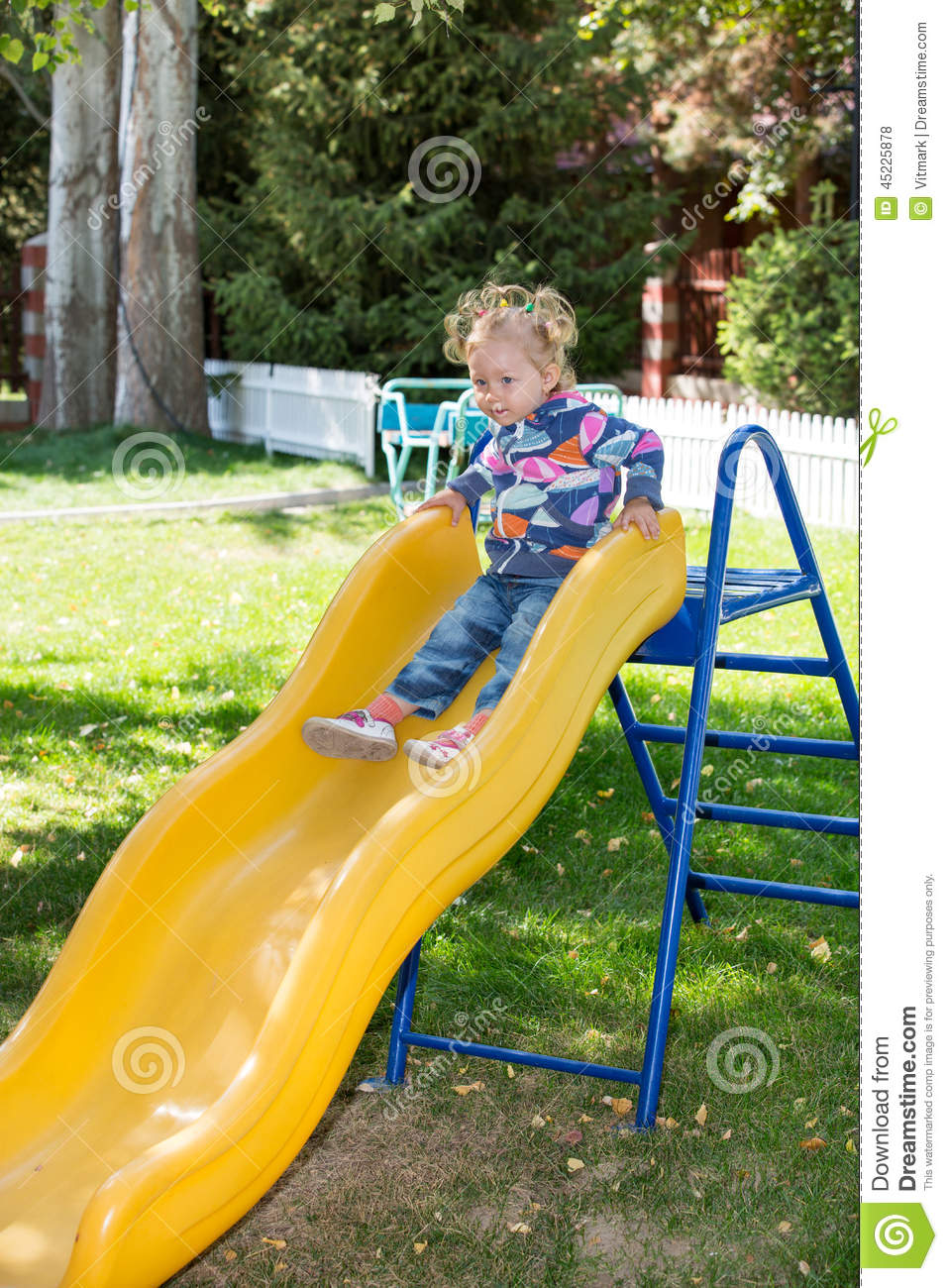 Happy Adorable Girl On Childrens Slide On Playground Near