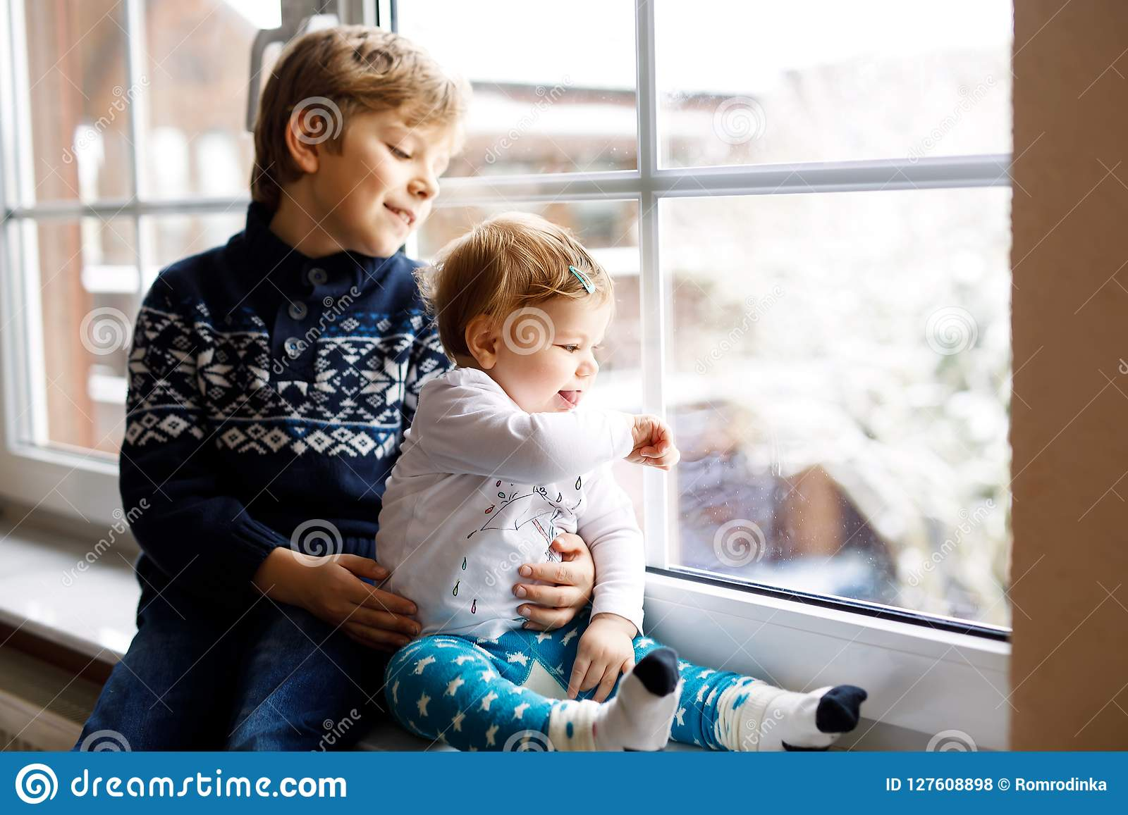 15a58416b Happy Adorable Kid Boy And Cute Baby Girl Sitting Near Window And ...
