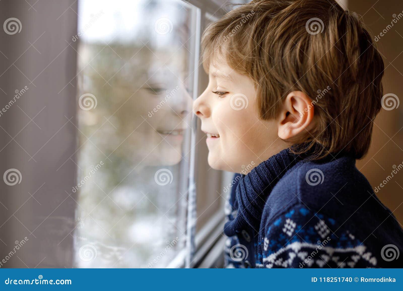 9b9fd4bd6 Happy Adorable Kid Boy Sitting Near Window And Looking Outside On ...