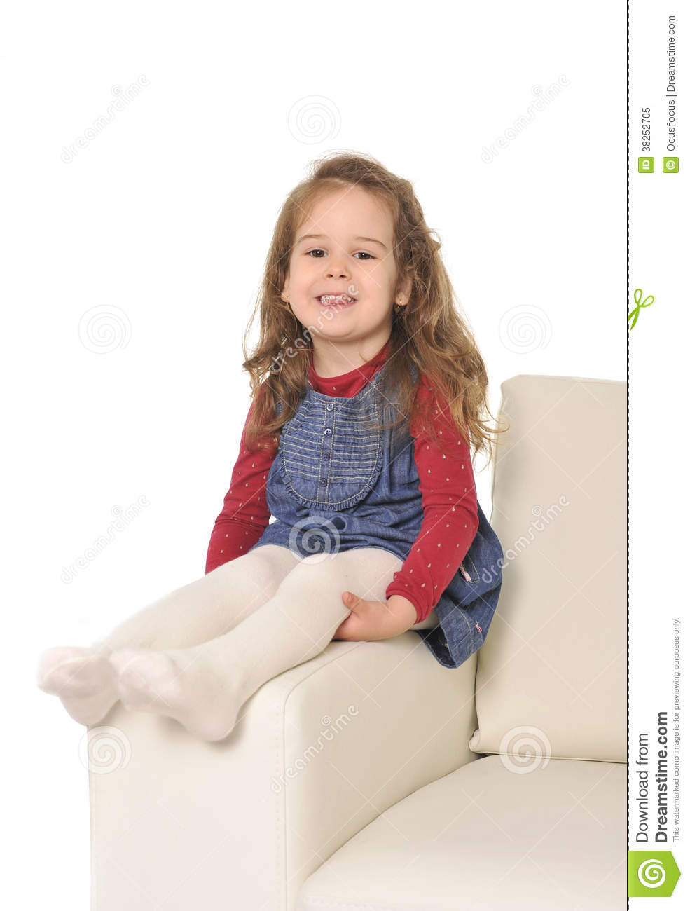 Happy adorable little girl with long hair sitting on the arm of couch