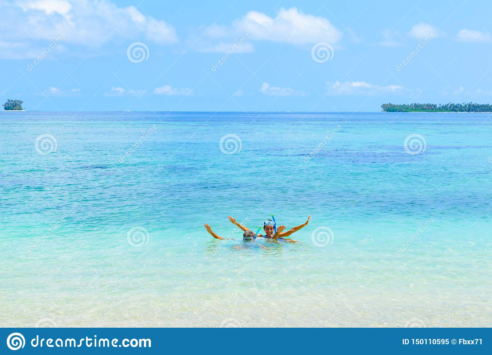 Happy adult couple having fun in turquoise water wearing snorkeling mask. Real people bathing in caribbean sea on tropical beach,