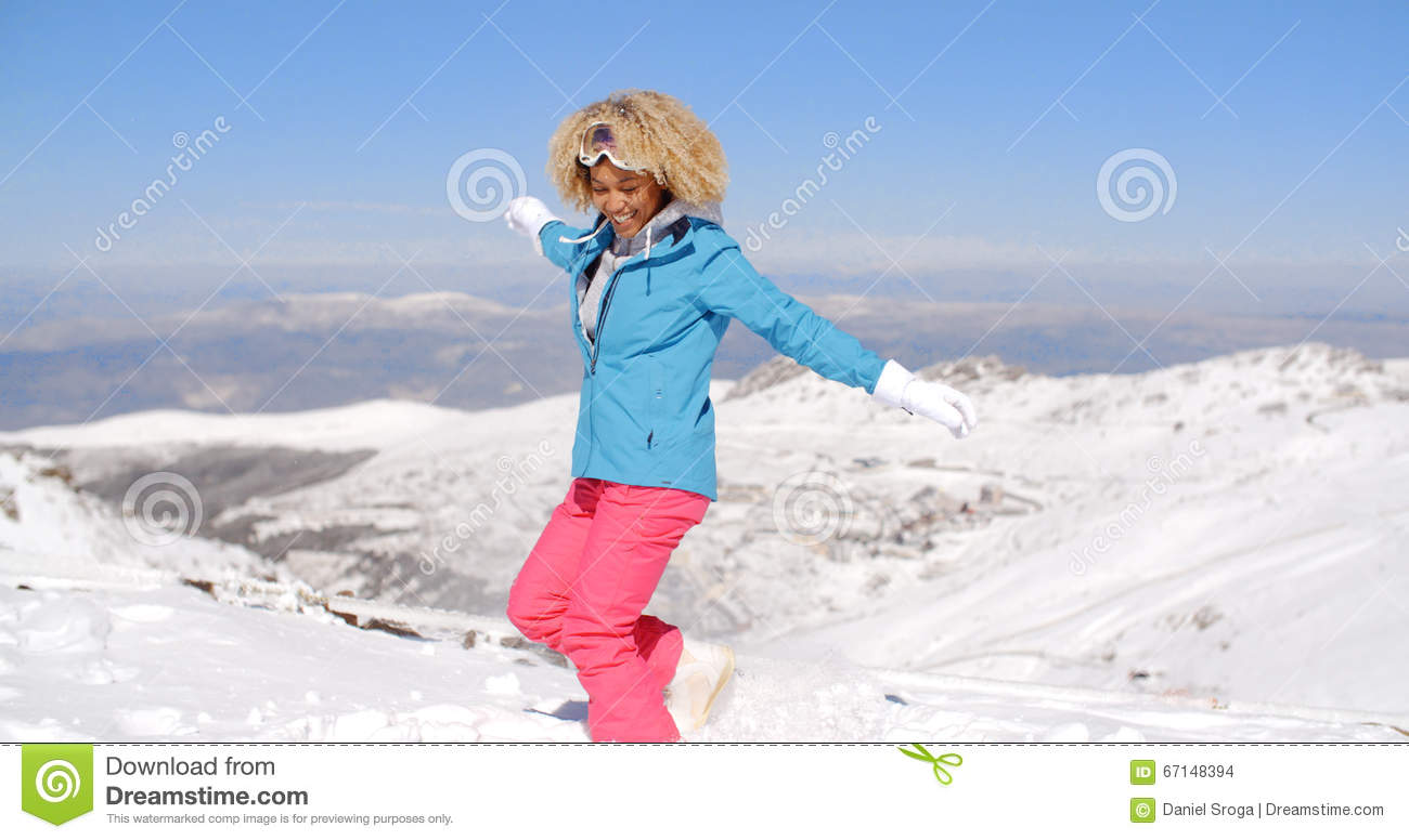 bf99be50eb Happy beautiful young adult female in pink and blue skiing outfit waving  arms around in the air near top of hill with mountain in background