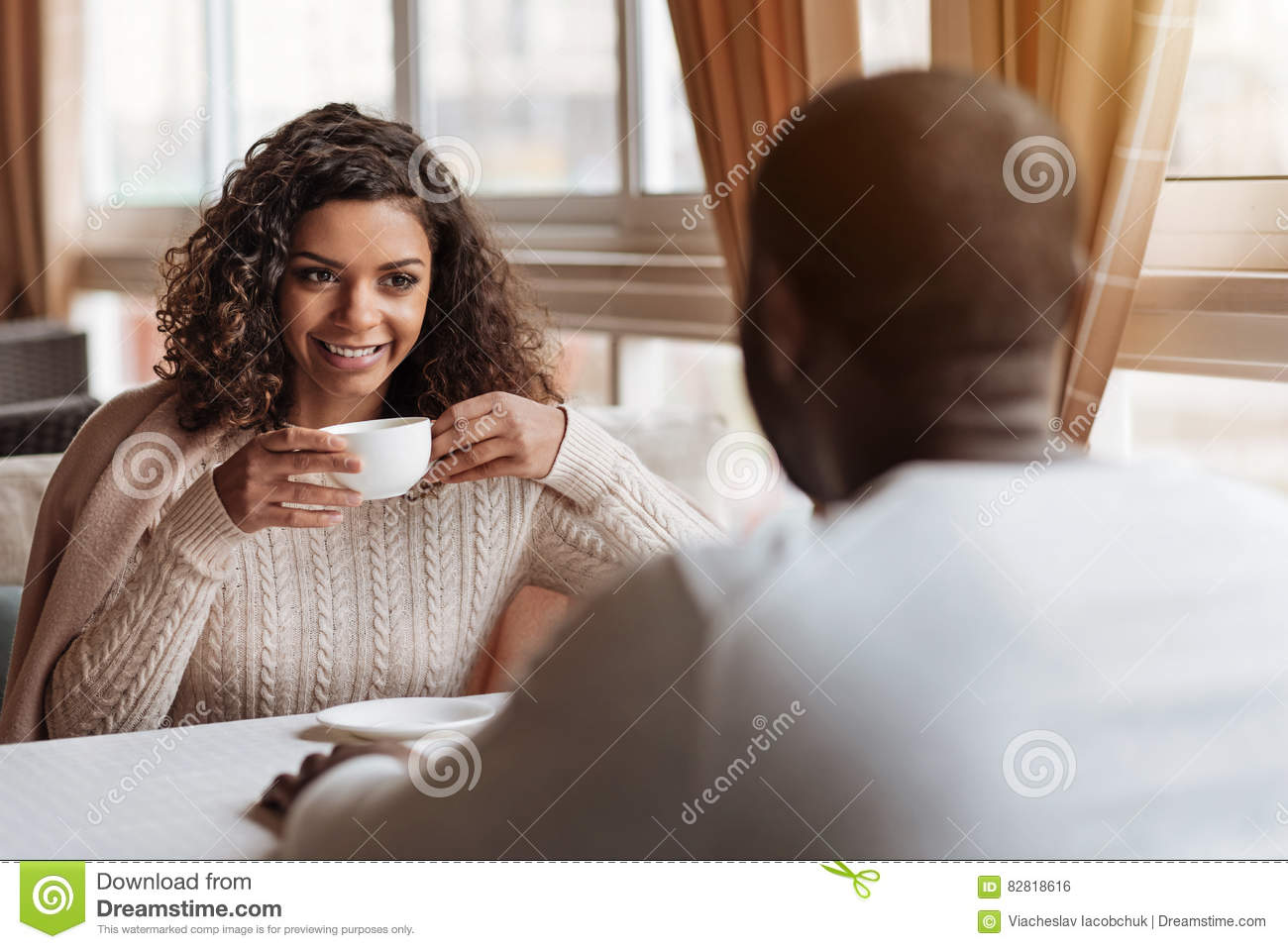 Happy African American couple drinking tea in the cafe