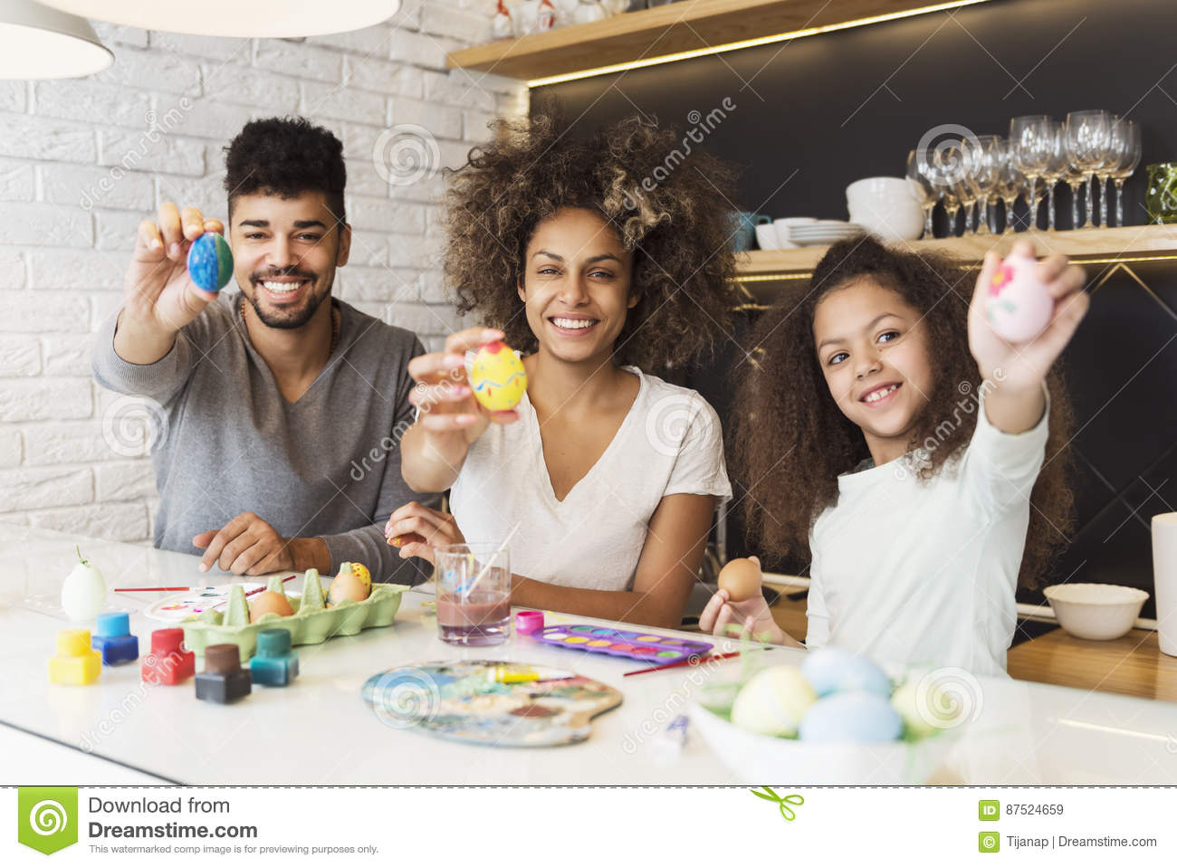 Happy African American family coloring eggs