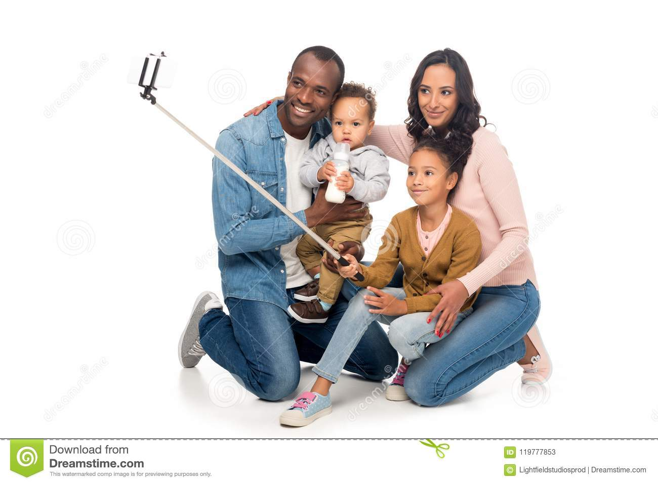 happy african american family with two kids taking selfie with smartphone