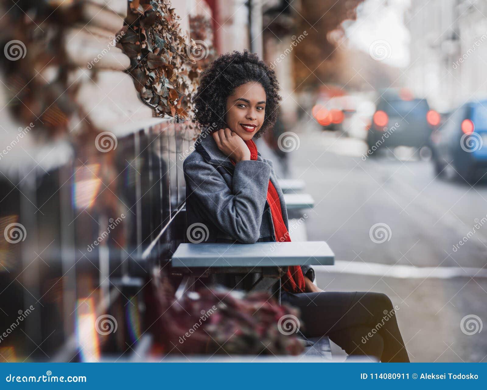 Happy African-American girl in the coat in steet cafe