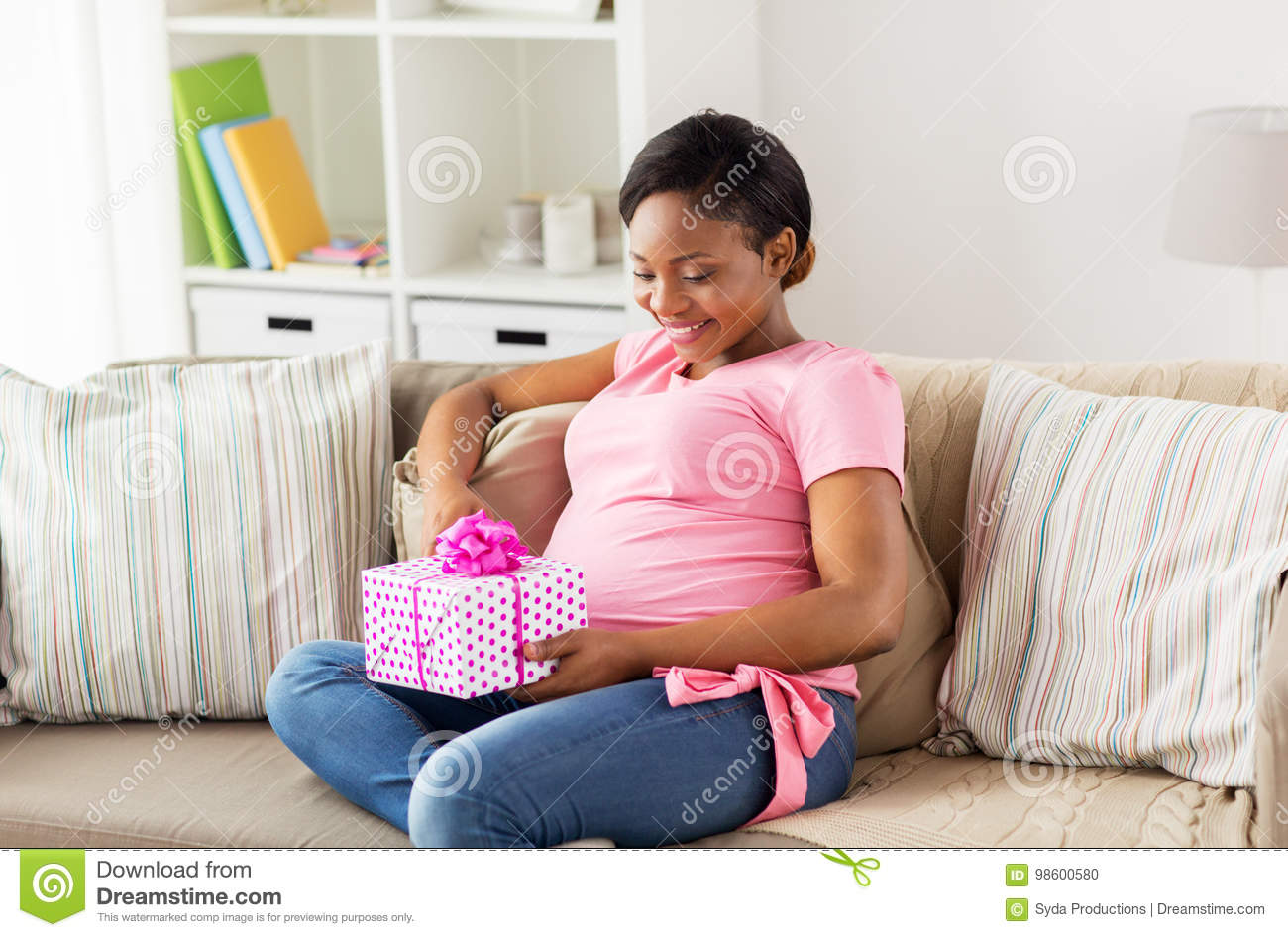 Happy african american pregnant woman with gift