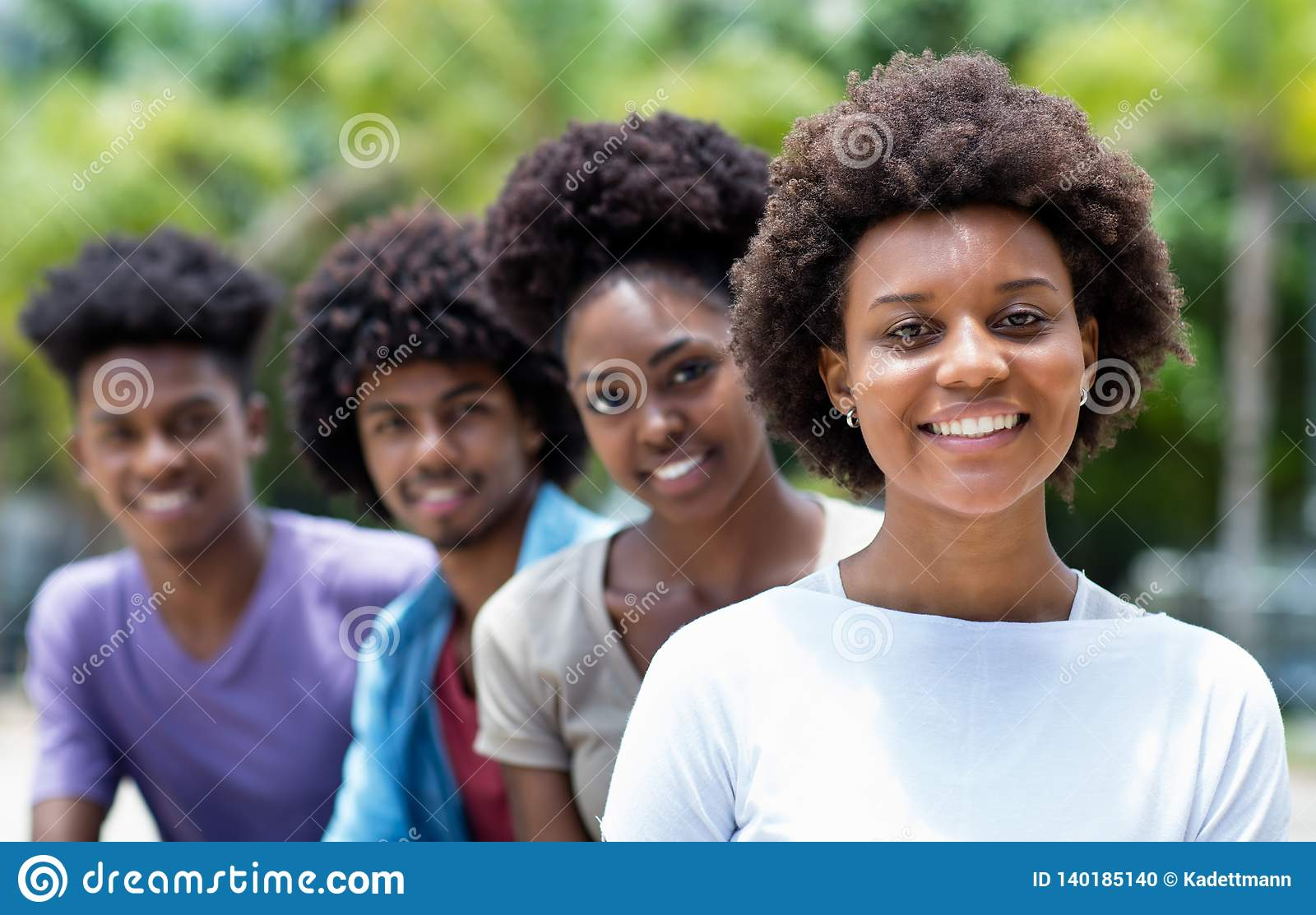 Happy african american woman with group of young adults in line