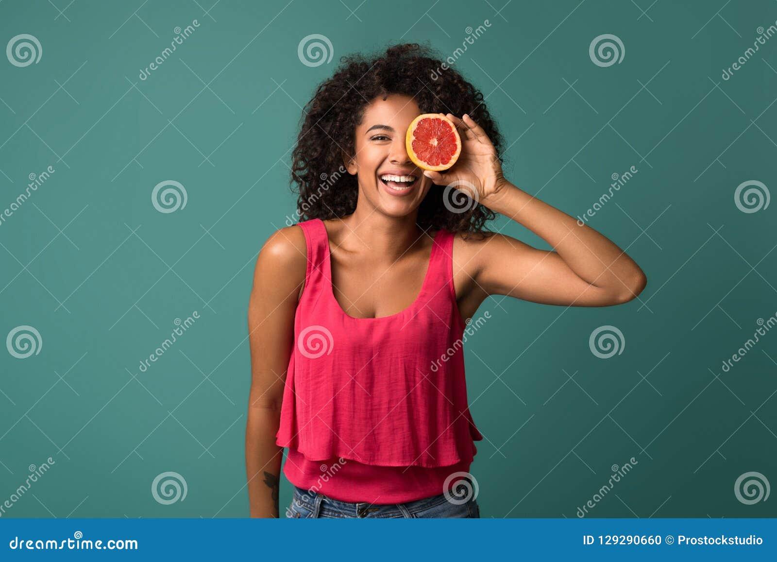 Happy african-american woman holding half of grapefruit