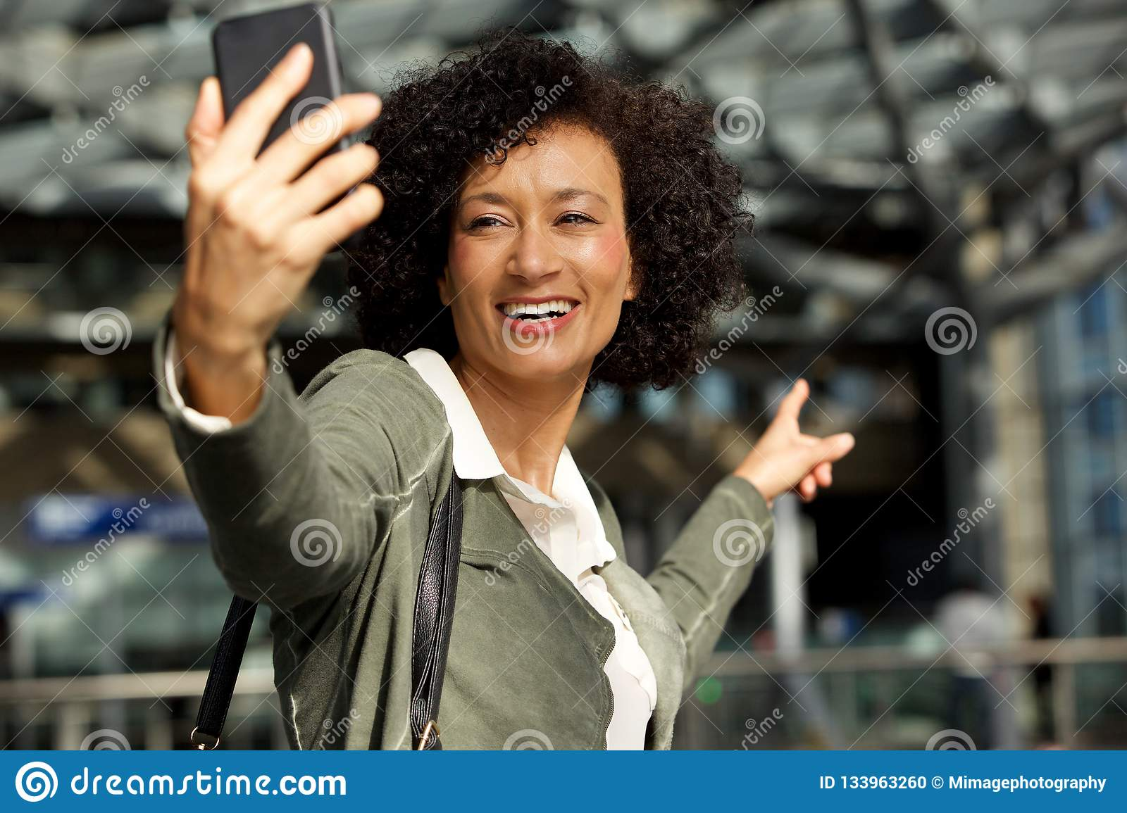 Happy african american woman taking selfie with cellphone and pointing