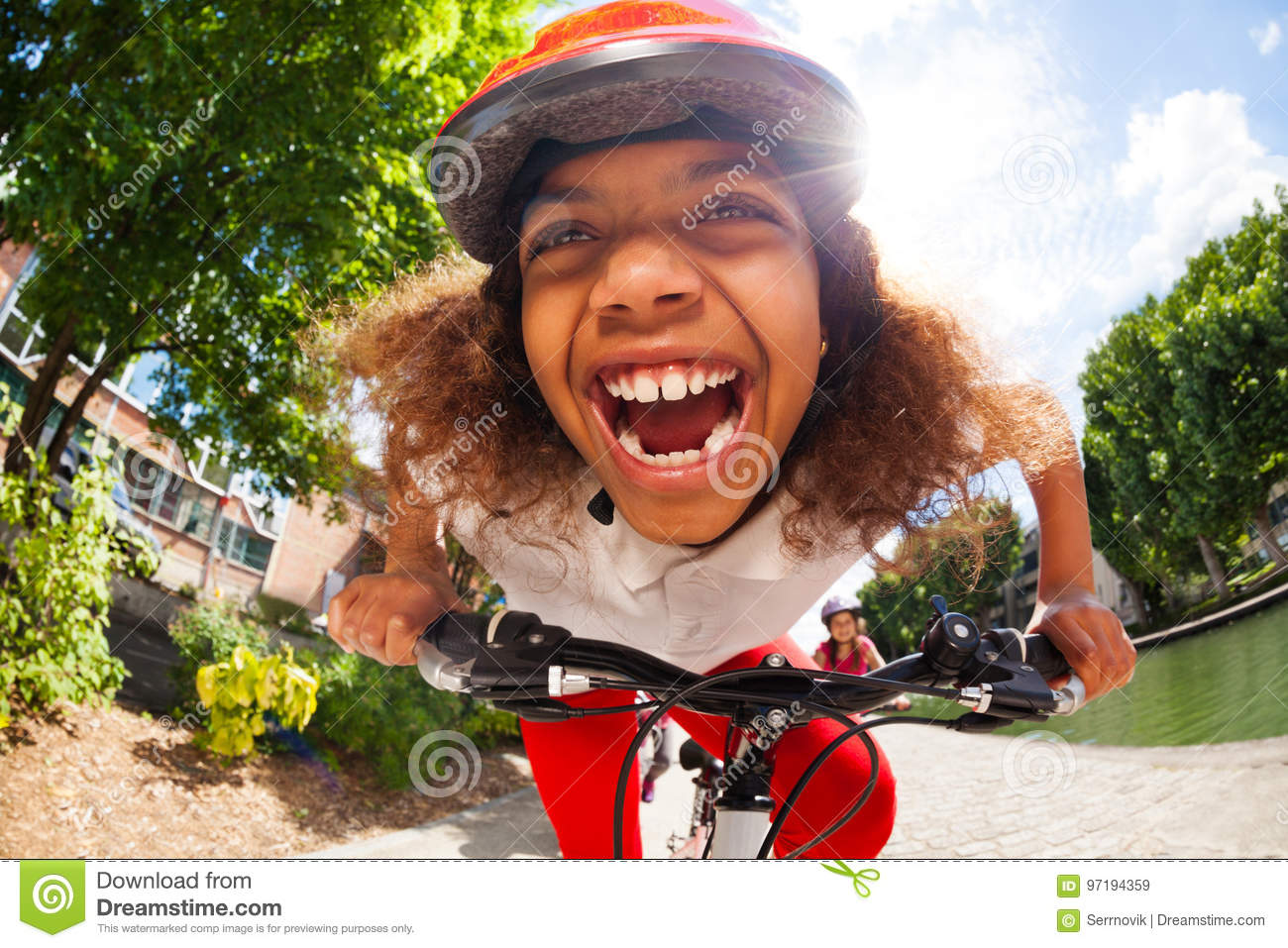 Happy African girl riding her bicycle at sunny day