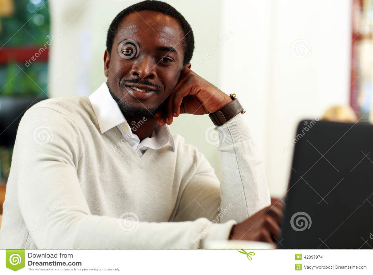 African Man Sitting At The Table Stock Photo