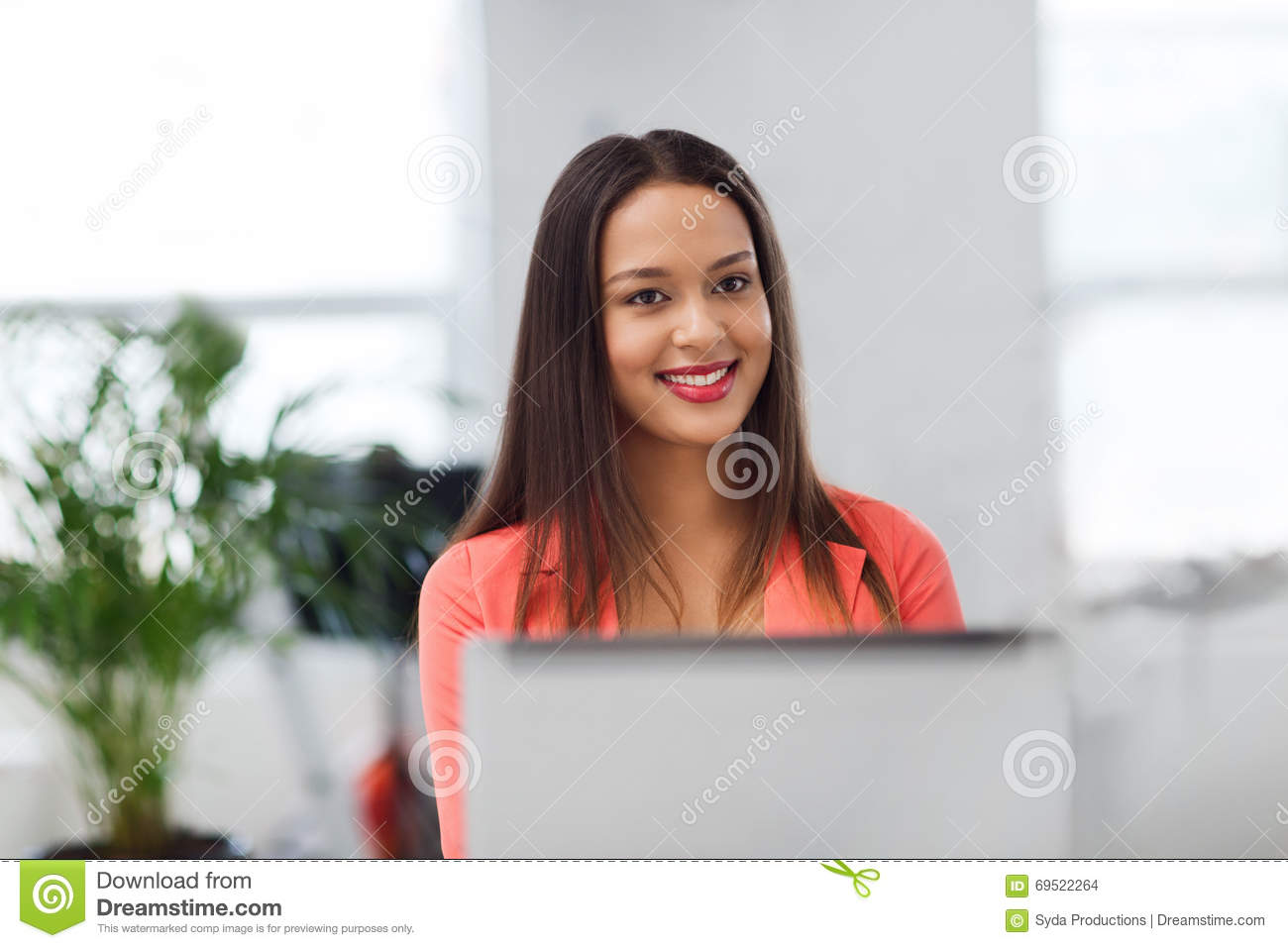 Happy african woman with laptop computer at office