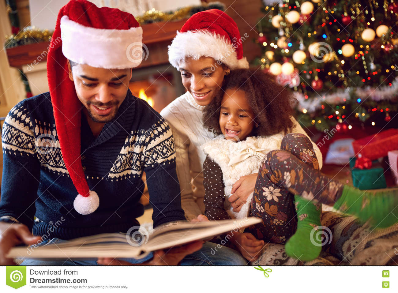 Happy afro American family read a book at fireplace on Christmas