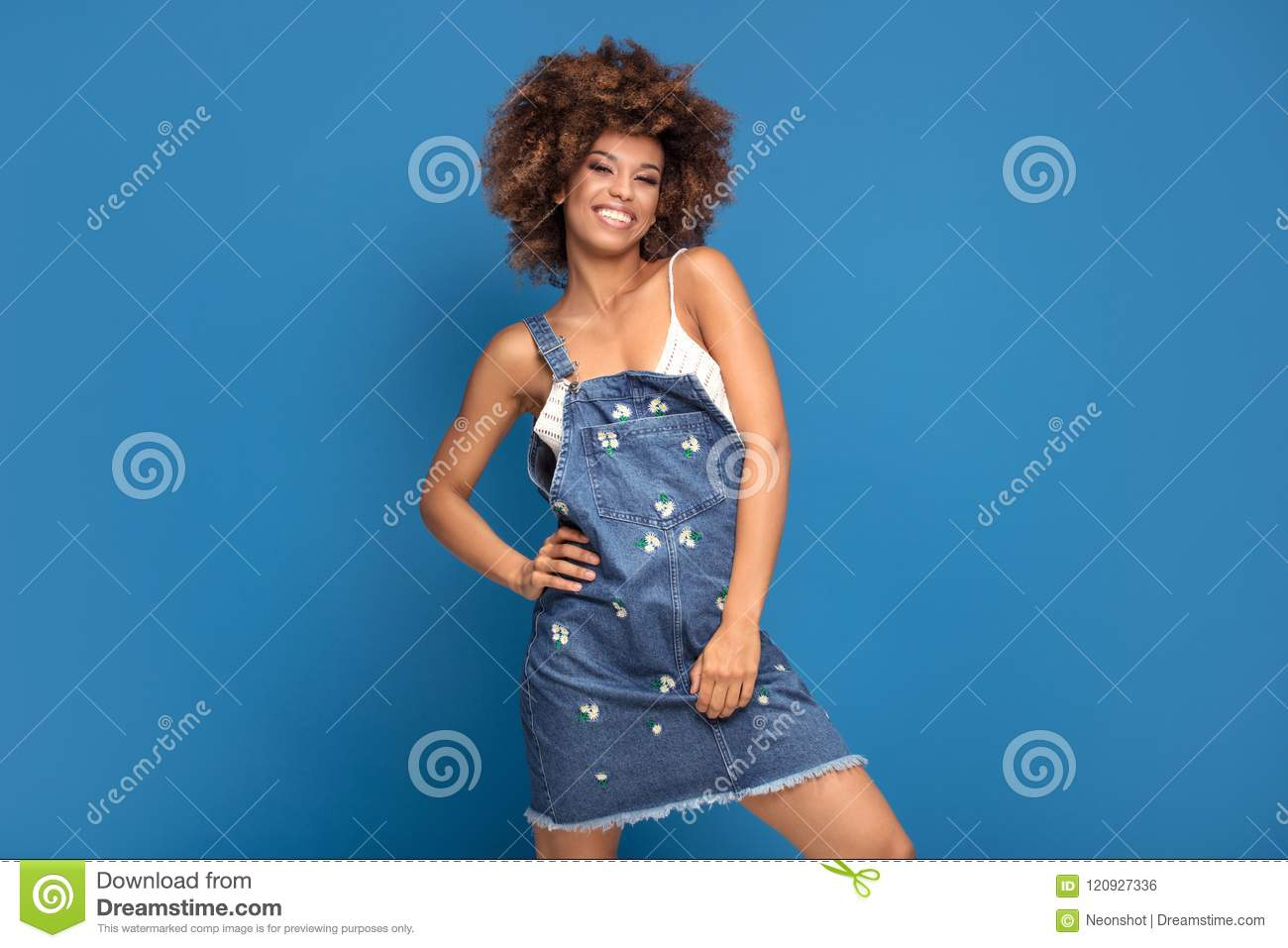 Happy Afro Girl In Jeans Dress On Blue Background Stock Photo
