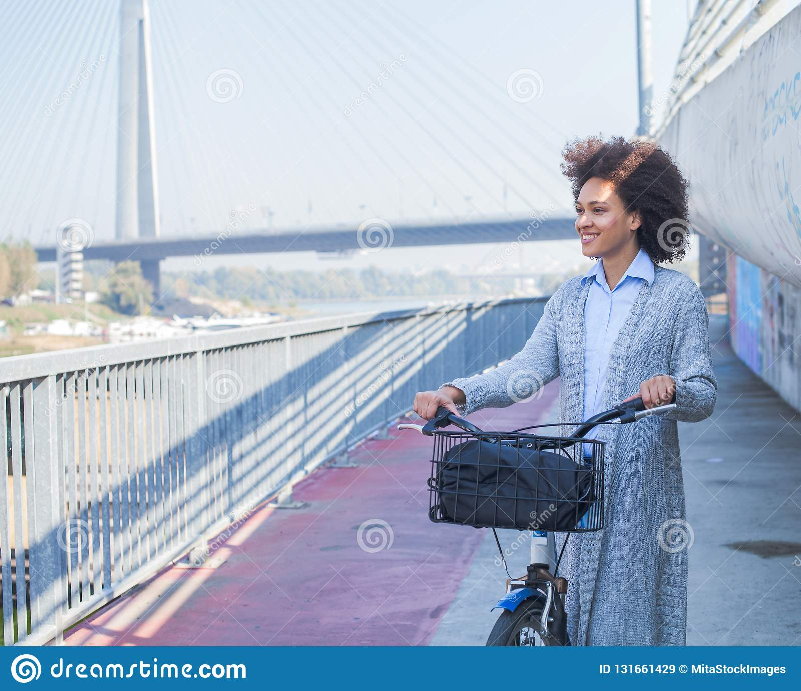 Happy Afro young woman with bicycle