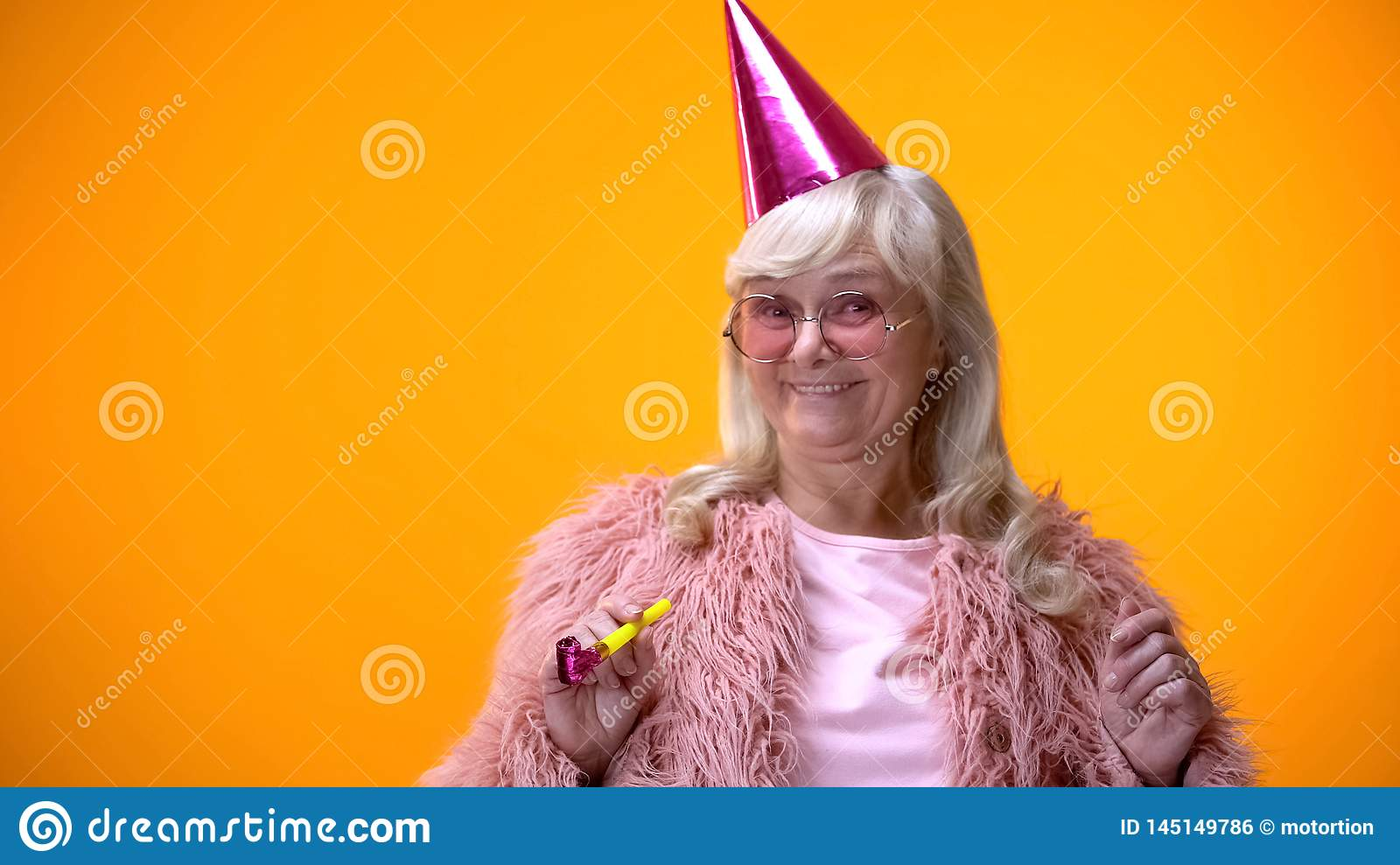 Happy aged woman in pink coat and round glasses celebrating birthday anniversary