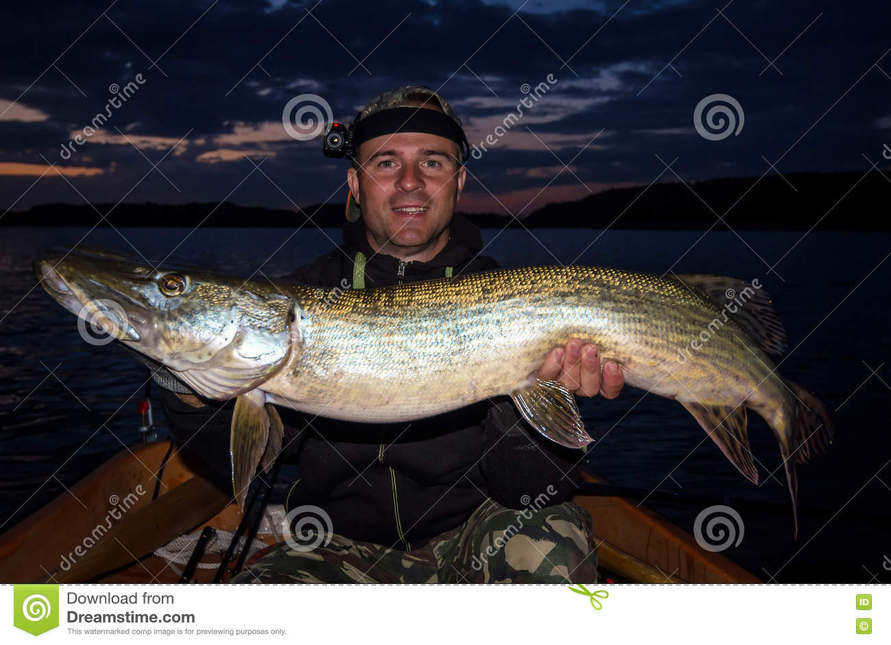 Happy angler with monster pike at evening time