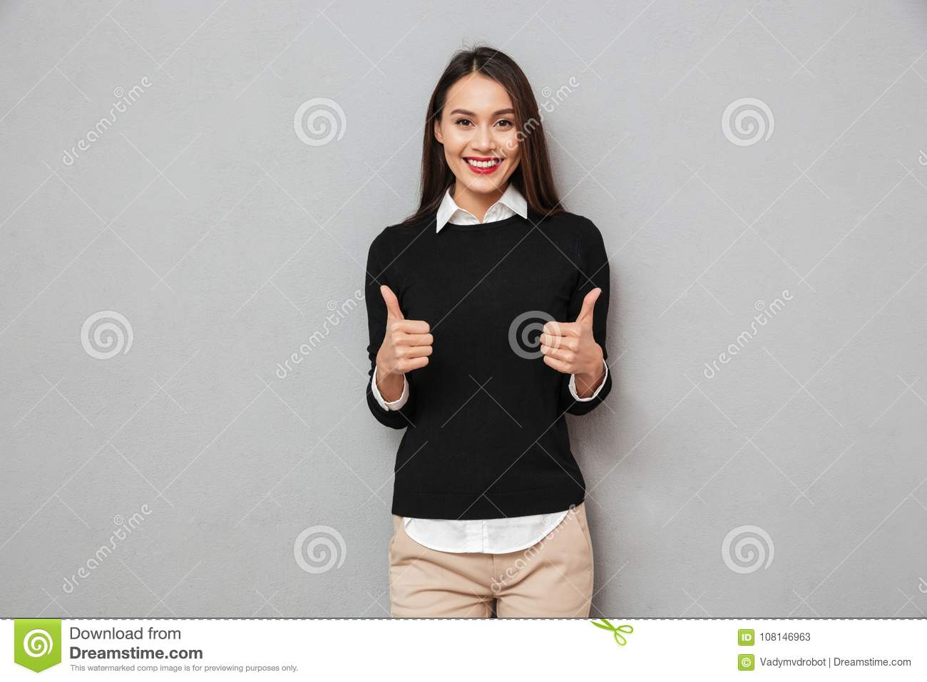 Happy asian business woman in business clothes showing thumbs up
