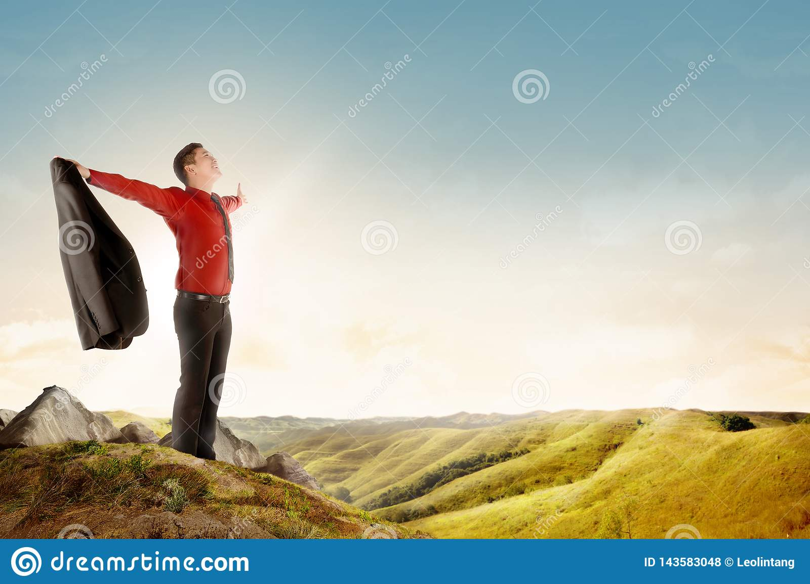 Happy asian businessman holding a suit standing on top of mountain celebrate his successful