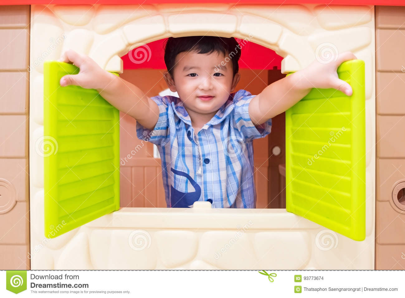 Happy Asian child Boy playing window toy house in playground