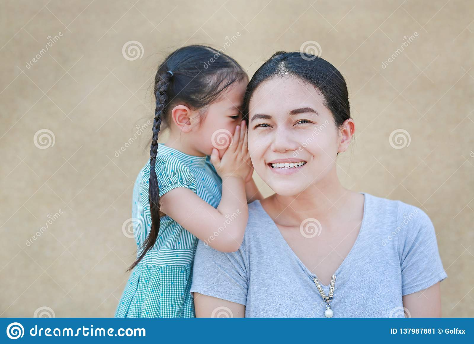 Happy Asian child girl sharing a secret to her mom. Kid girl whispering gossip a something to mother ear