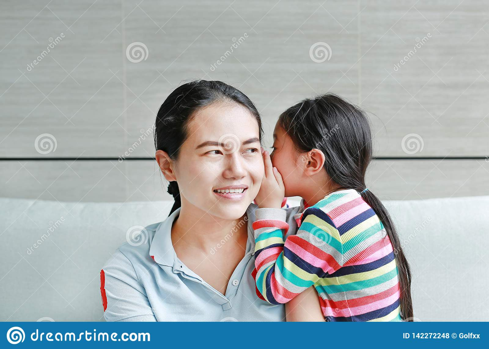 Happy Asian child girl sharing a secret to her mom in the living room at home. Kid girl whispering gossip a something to mother