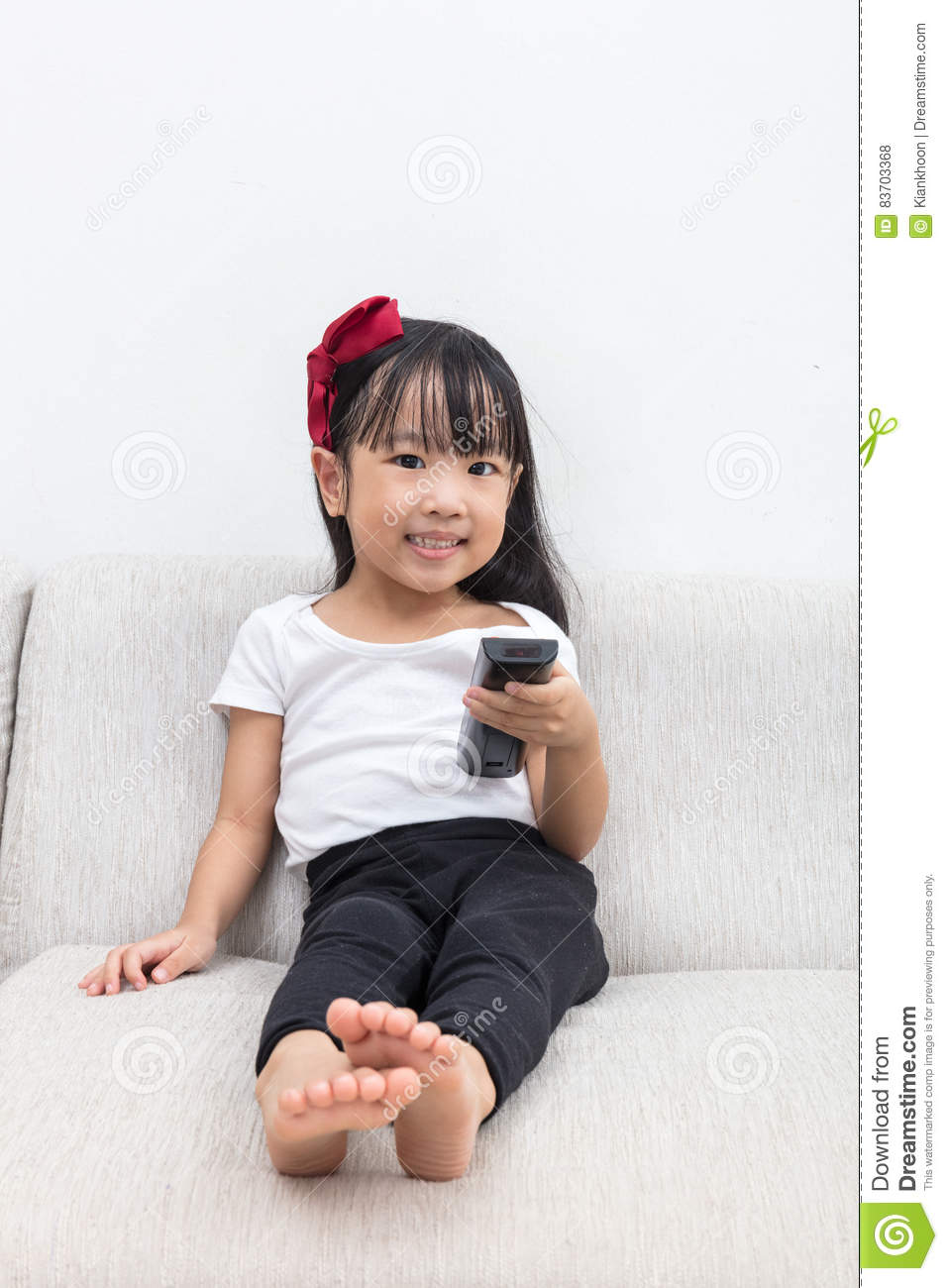 Happy Asian Chinese Little Girl Holding A TV Remote Control Stock Photo