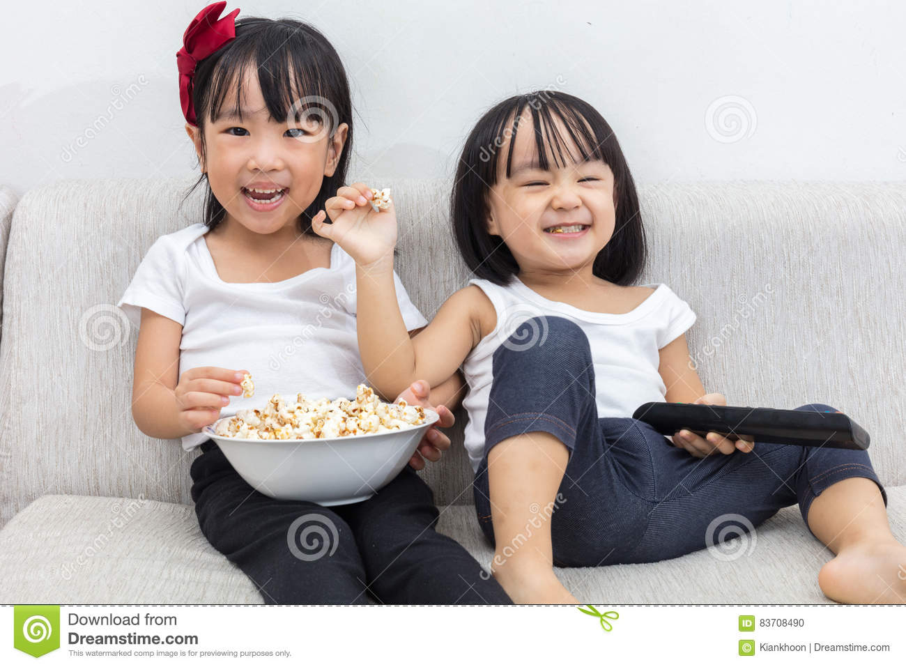 Happy Asian Chinese Little Sisters Eating Popcorn On The Sofa Stock Photo