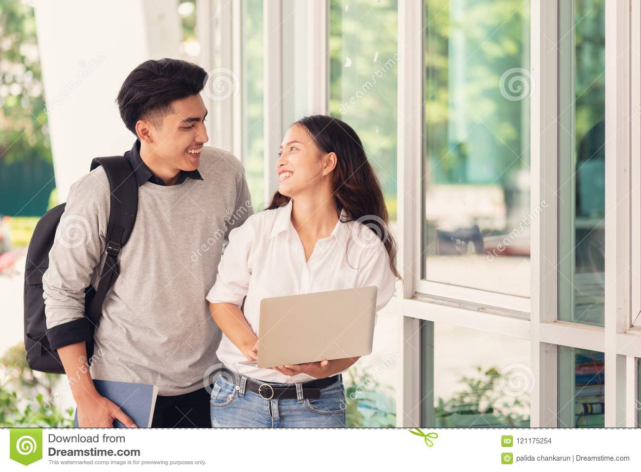 Happy Asian couples students or colleagues use laptop computer a