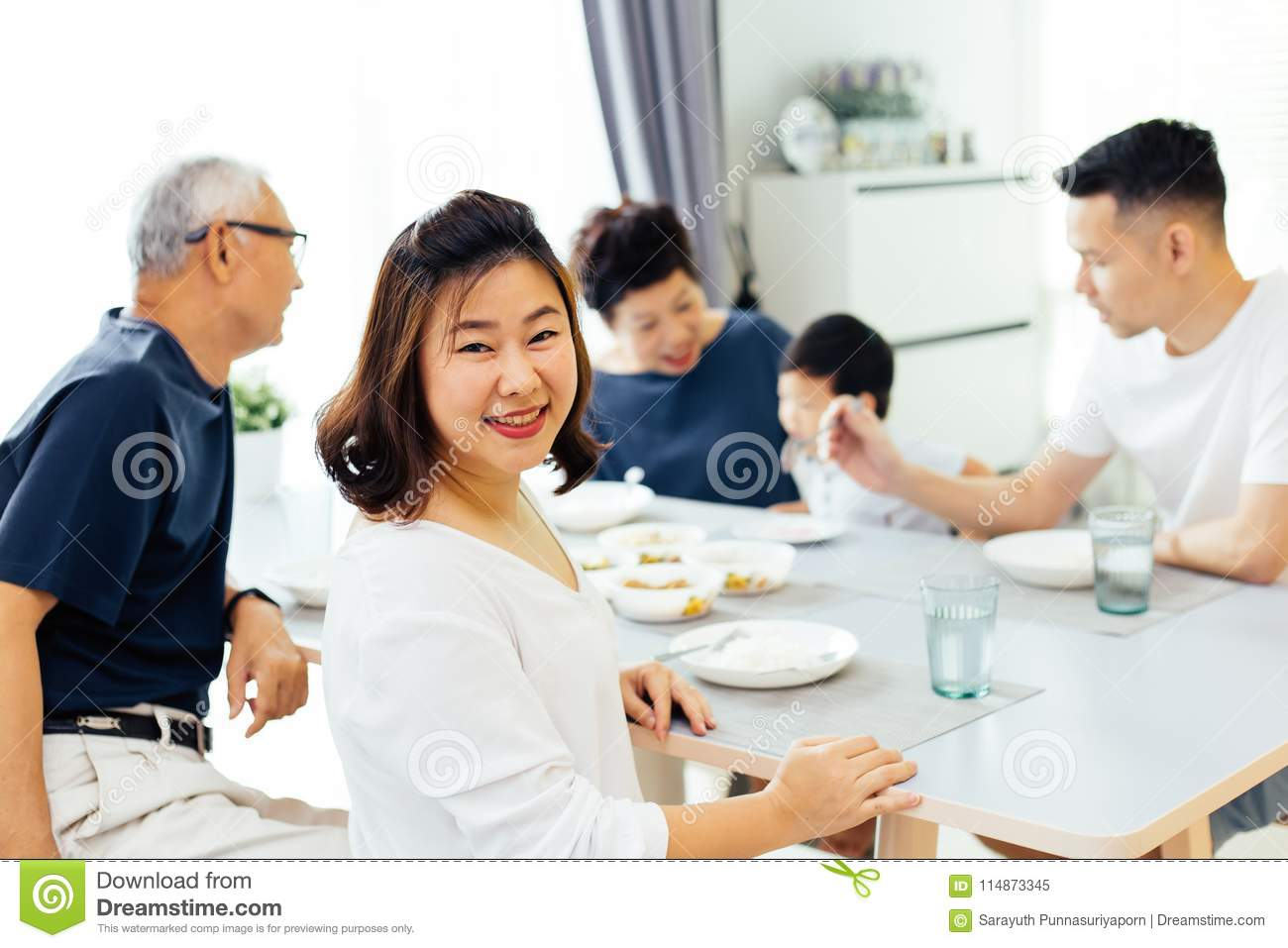 Happy Asian extended family having dinner at home full of happiness and smiles.