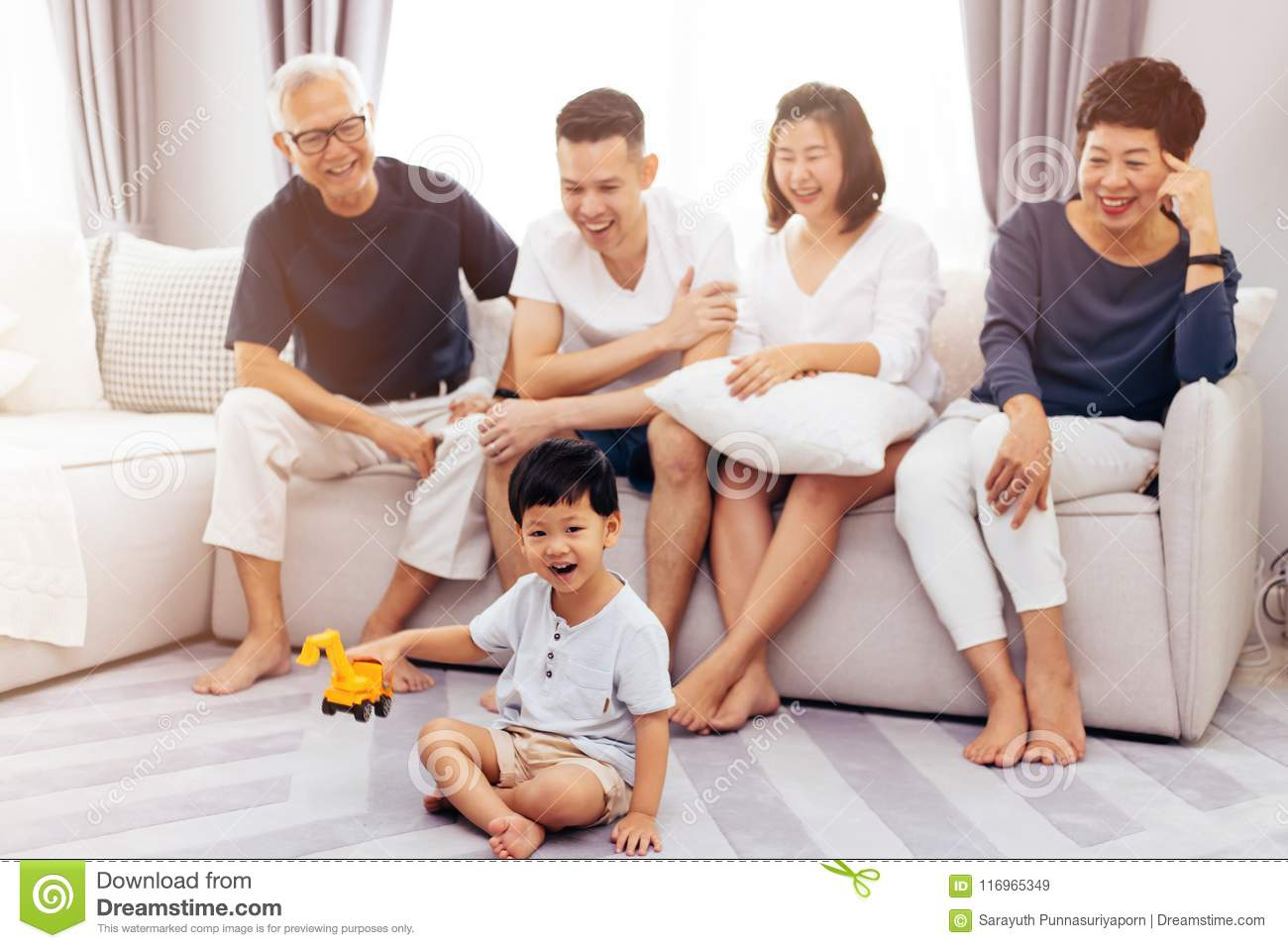 Happy Asian extended family sitting on sofa together and watching little child playing toy on the floor with happiness.