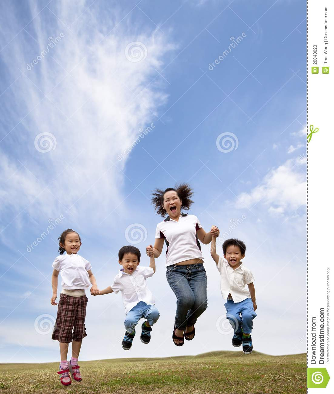 Happy asian family jumping on the grass
