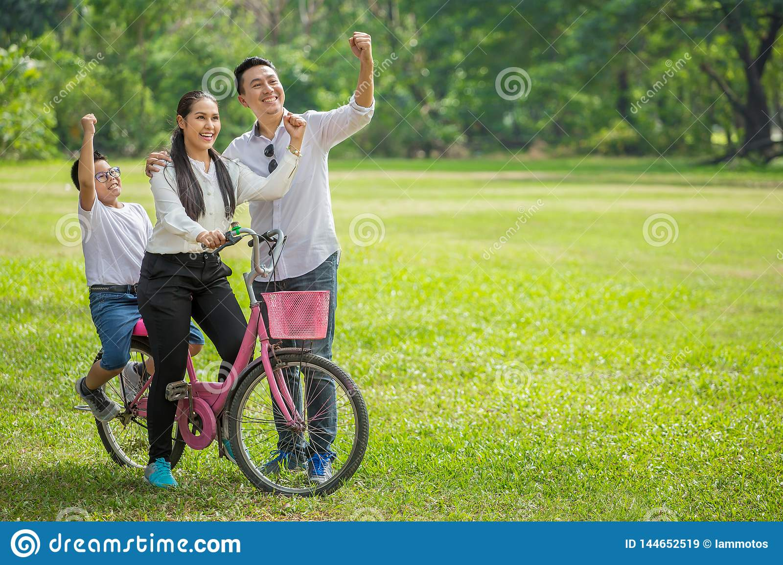 happy asian Family, parents and children riding bike hands up in park together. father ,mother ,son on bicycle having fun