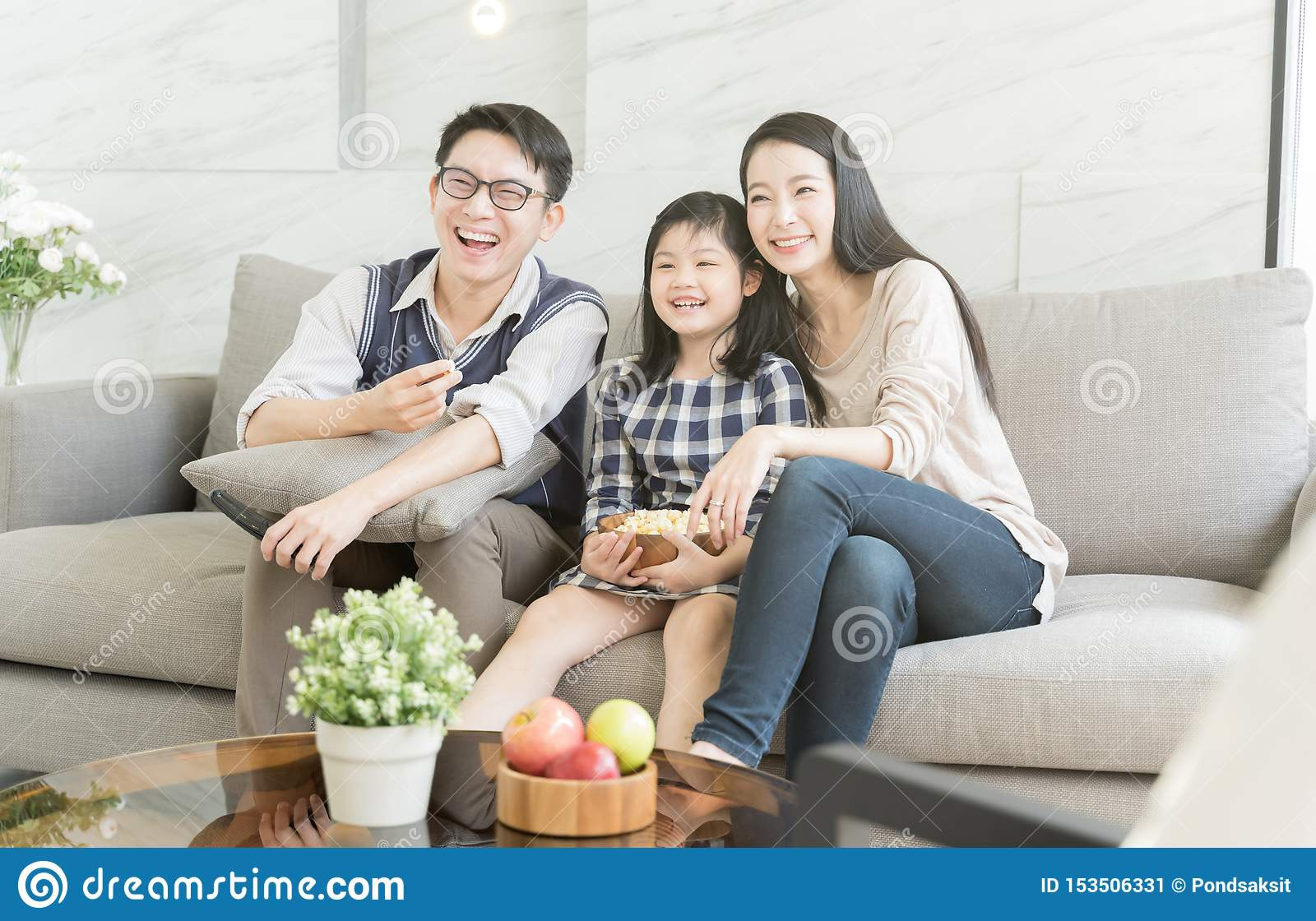 Happy Asian Family Watching Tv Together On Sofa In Living ...