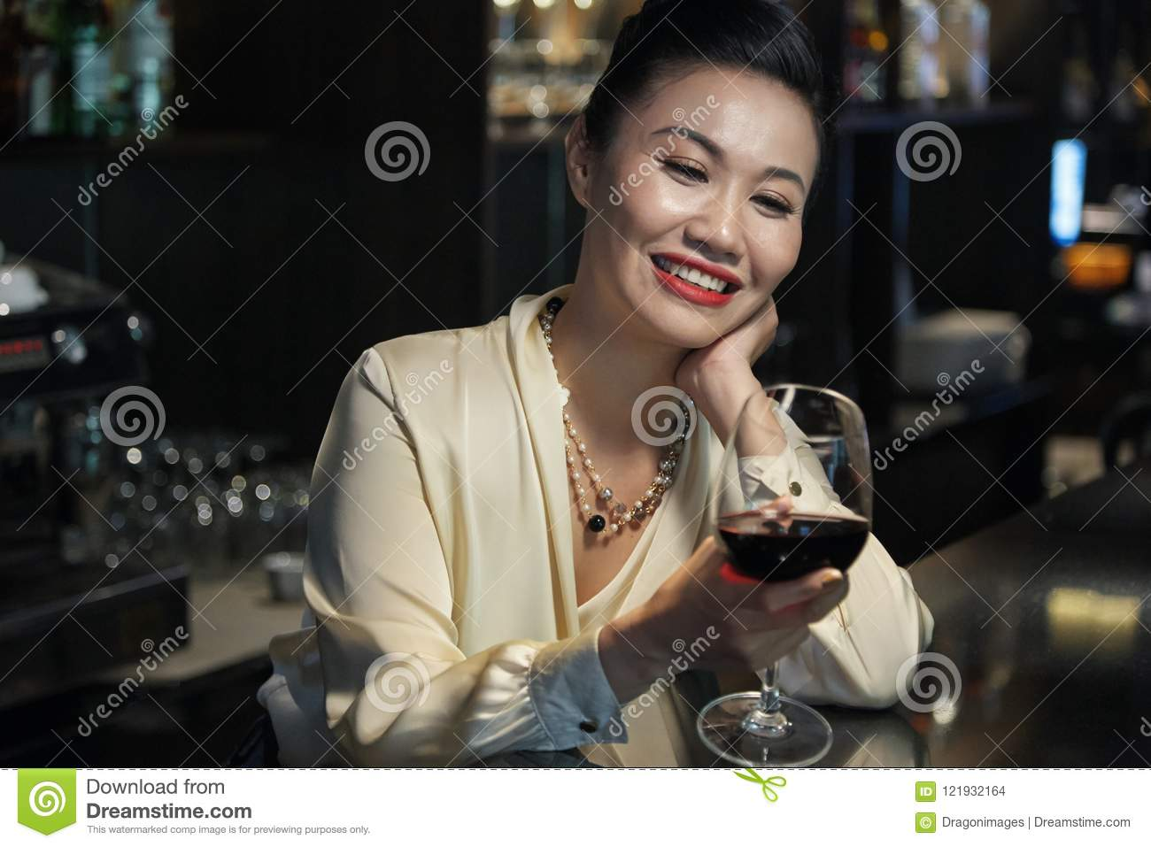Happy Asian female looking at wine glass