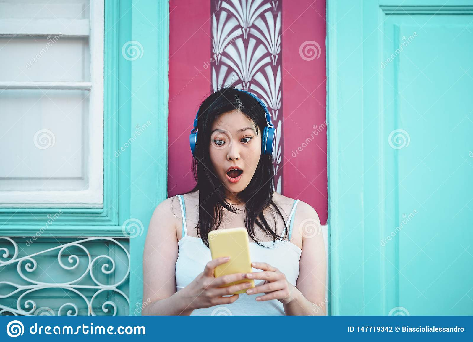 Happy Asian girl listening to music with headphones outdoor - Young Chinese woman playing her favorite playlist music