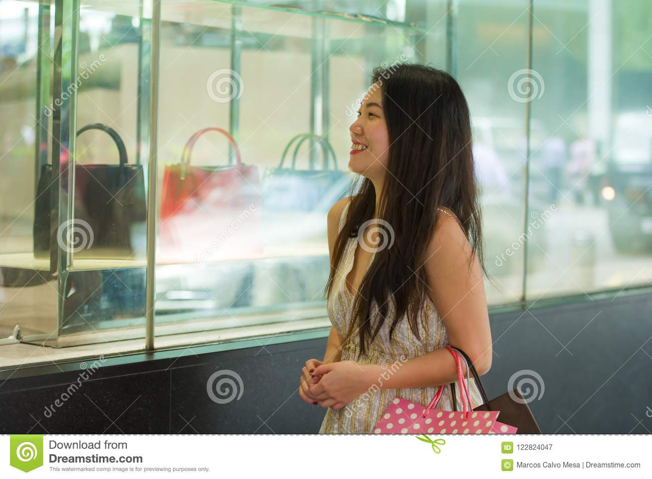 a8be95a225c Young beautiful and elegant happy Asian Korean woman holding shopping bags  after buying walking on street looking at clothing window store smiling  cheerful ...