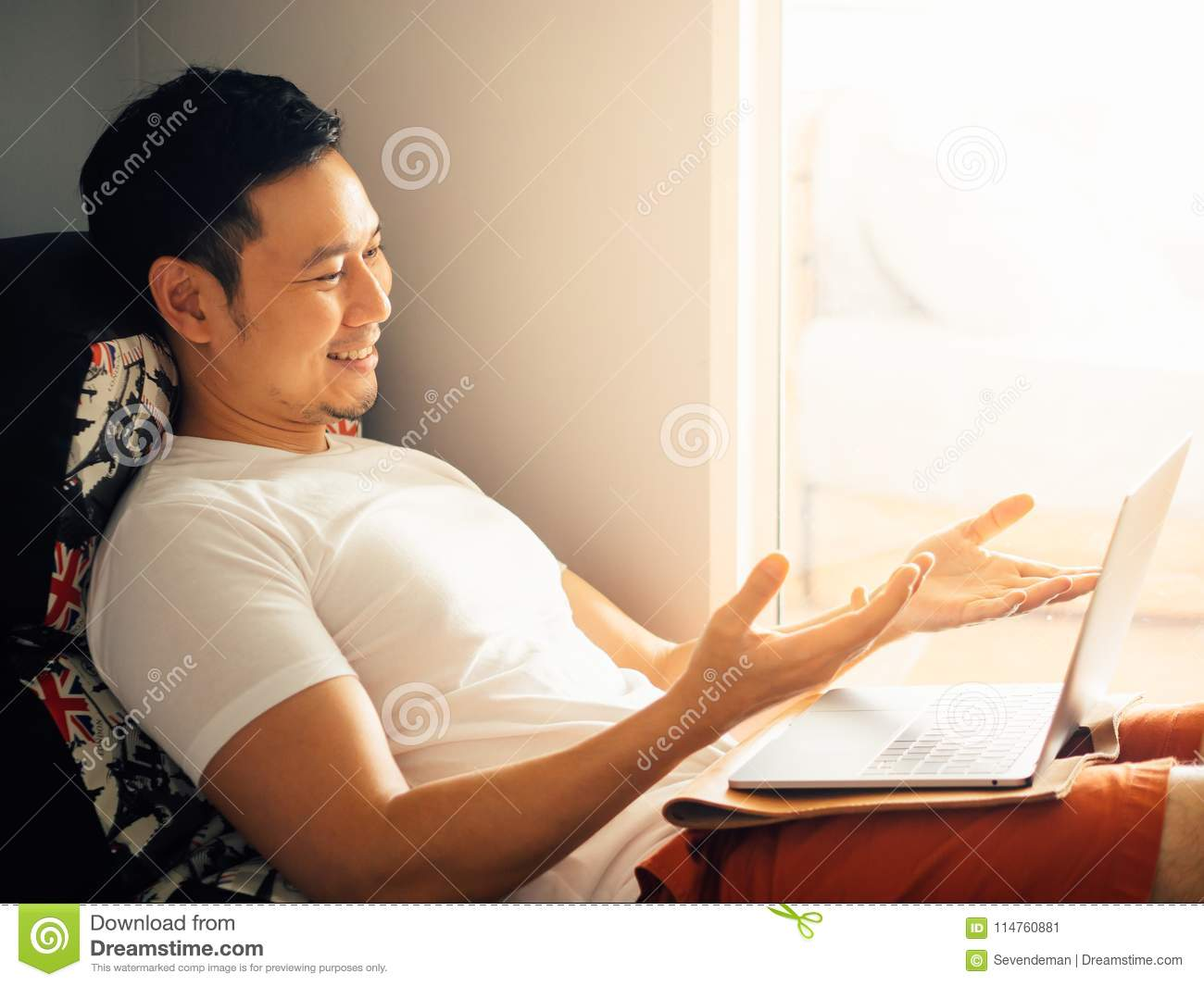 Happy man is using laptop and relax on sofa in the morning.