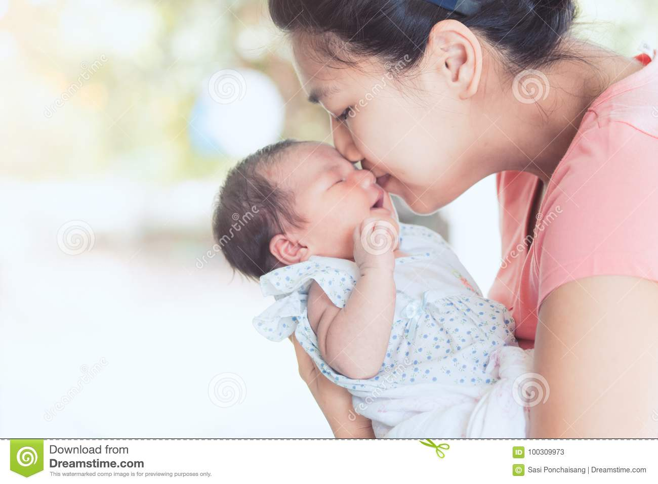 Happy asian mother hugging and kissing her newborn baby with love