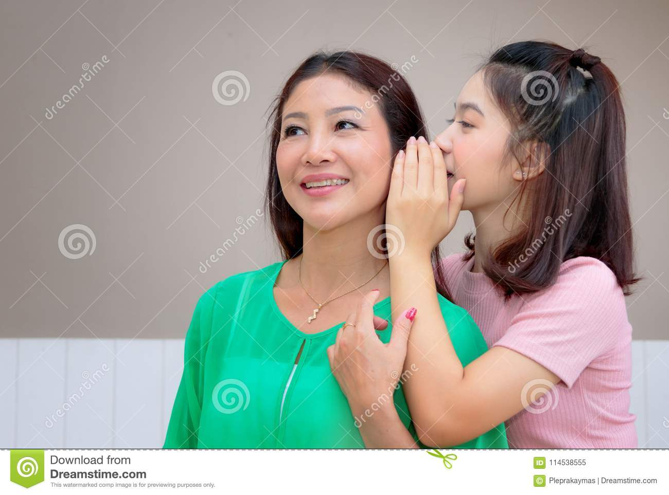 Asian mother and teen daughter whispering gossip