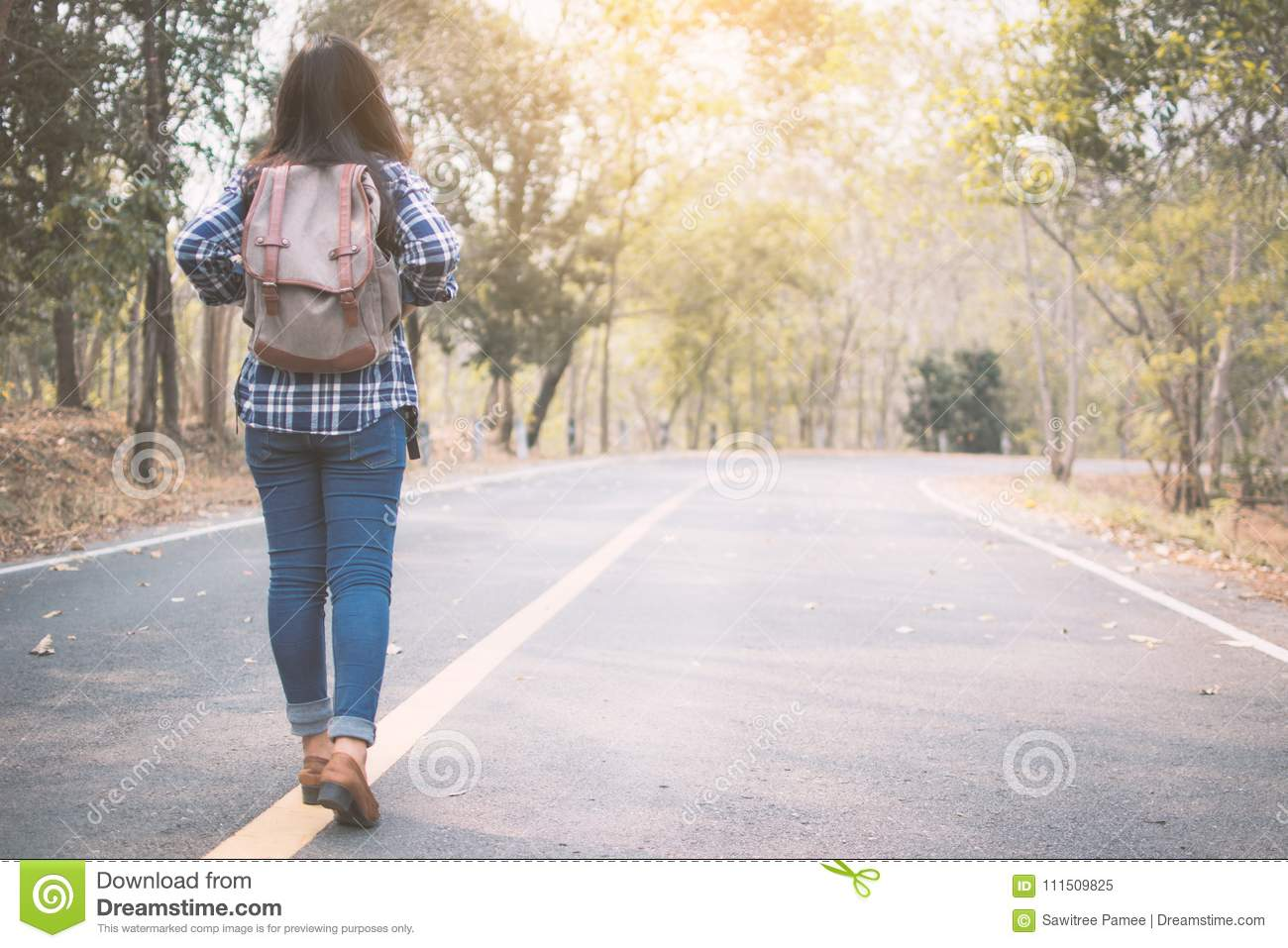 Happy Asian woman backpack in the road and forest background