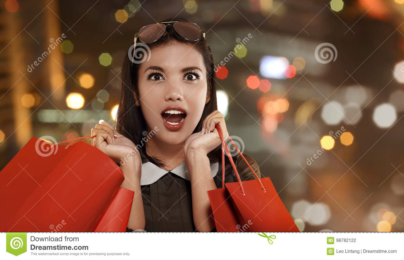Happy asian woman with red shopping bag celebrating Black Friday