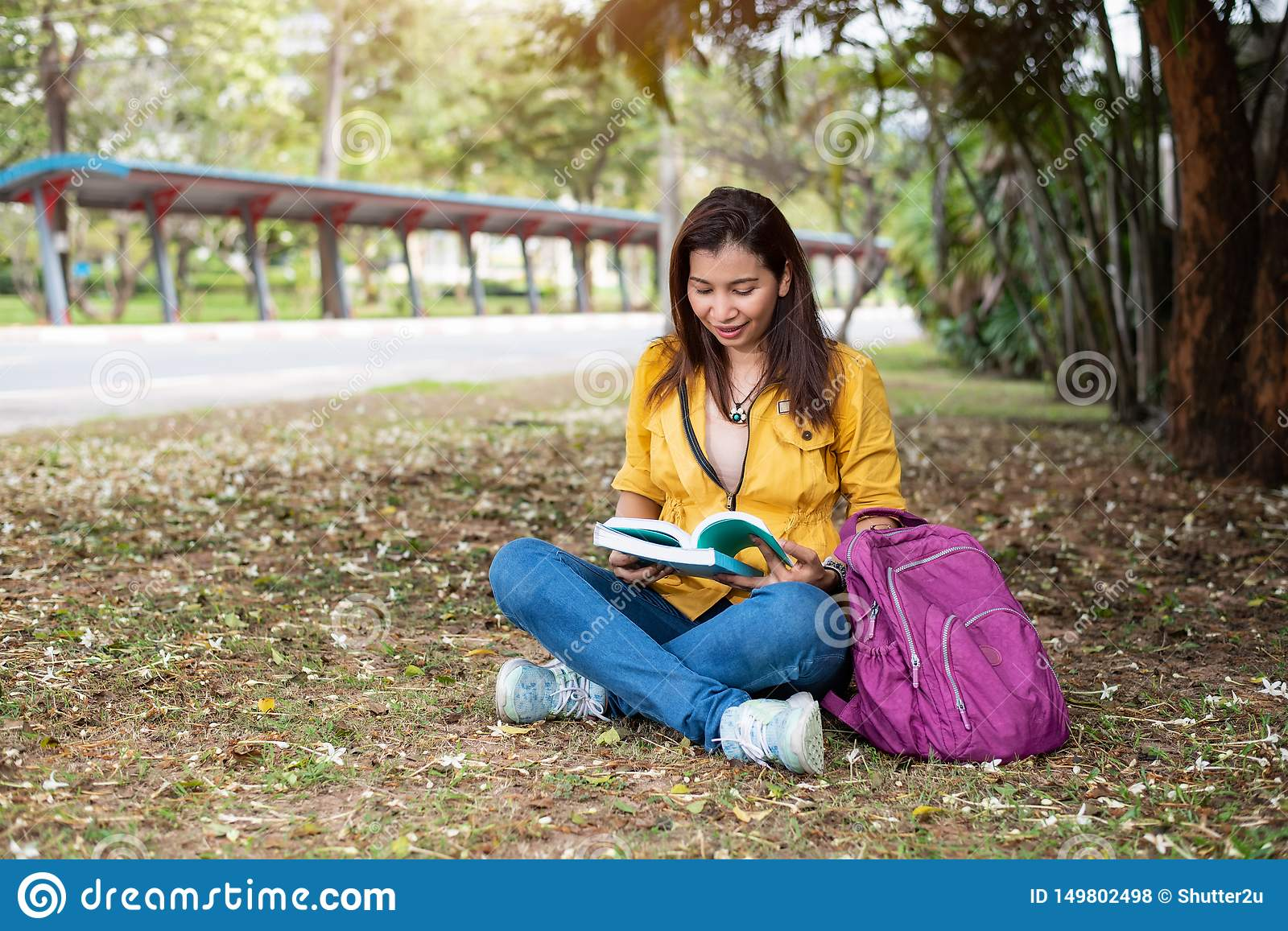 Happy Asian woman sitting and reading books in university park under big tree. People lifestyles and education concept. Summer