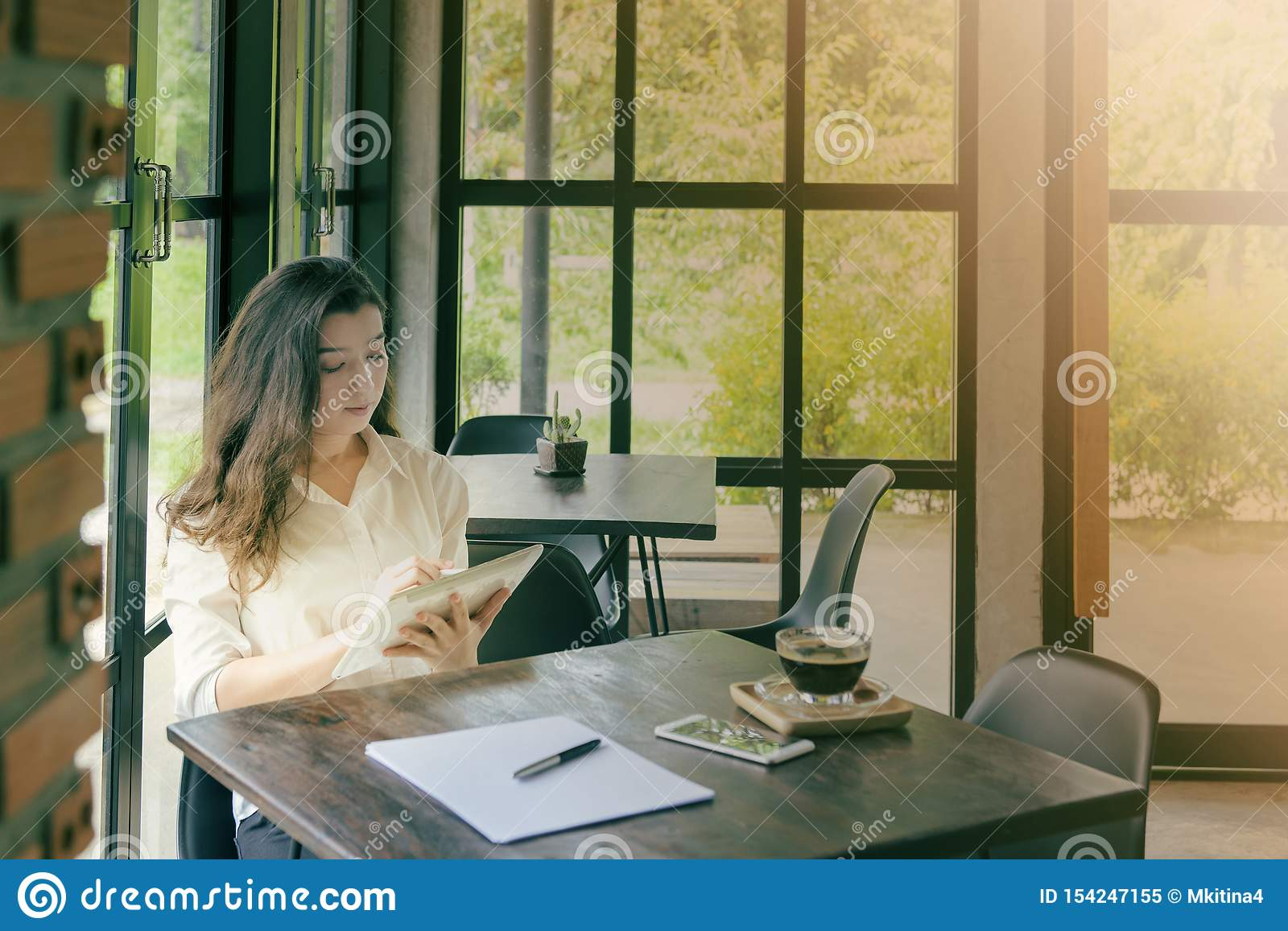 Happy asian woman using tablet computer in coffee shop with Vintage tone.E-commerce, university education, internet technology, or