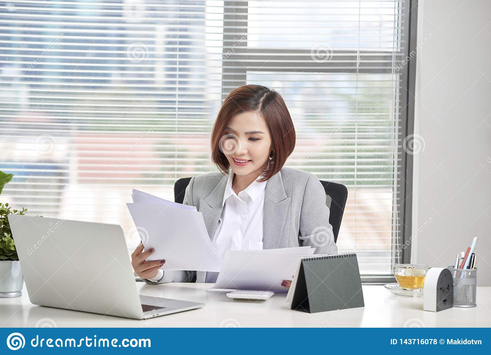 Happy asian woman working in office. Female going through some paperwork at work place