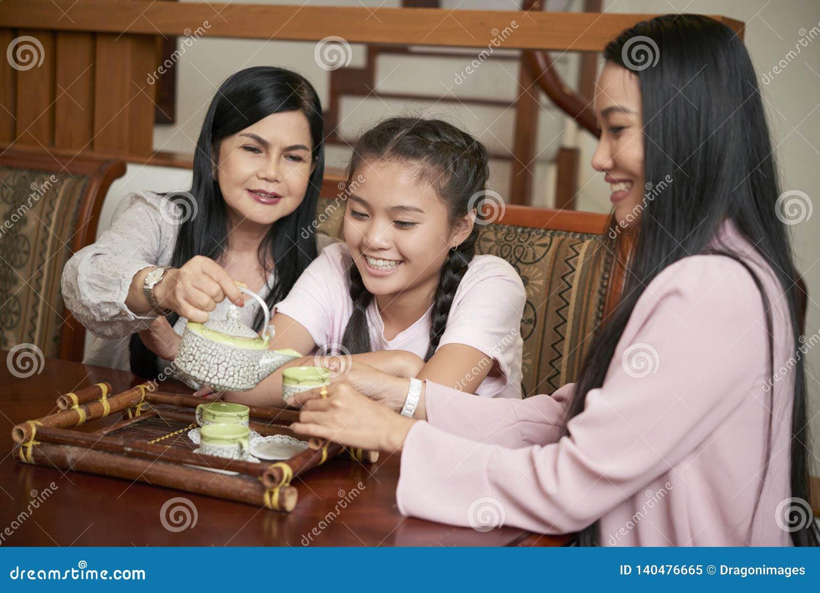 Happy Asian women of different generations having tea